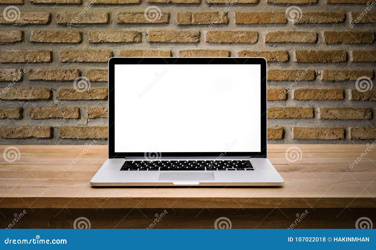 Computador moderno, portátil com a tela vazia no tijolo da parede
