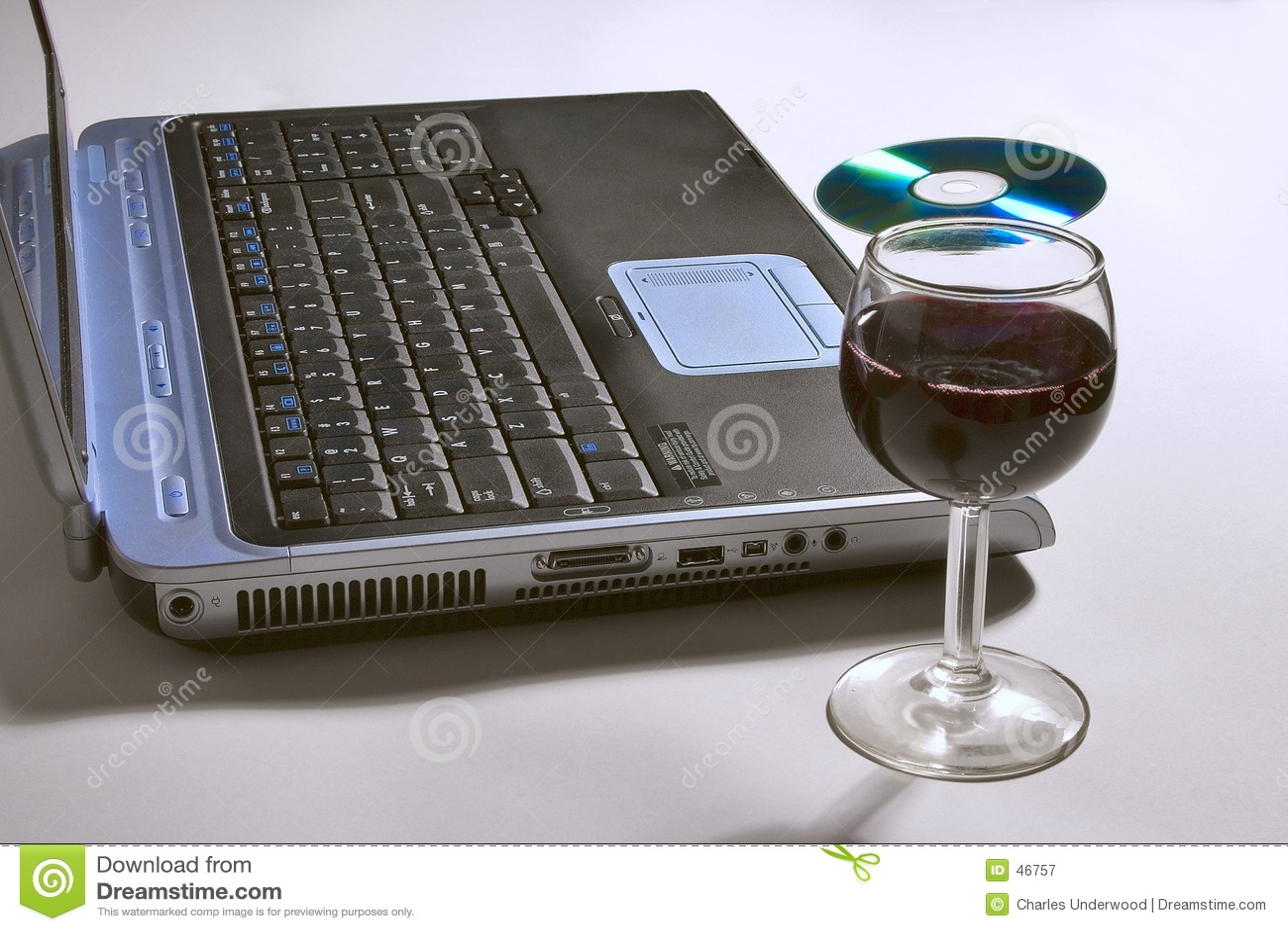 Computador portátil com um vidro do vinho e do CD.