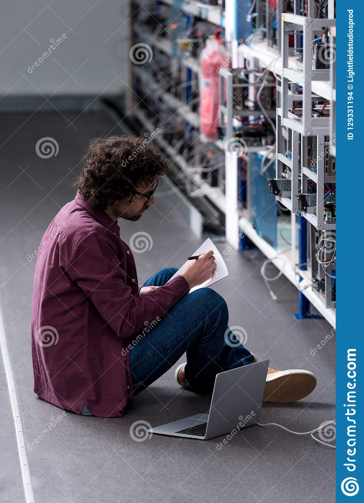 Computer engineer working while sitting on floor at cryptocurrency mining farm stock images