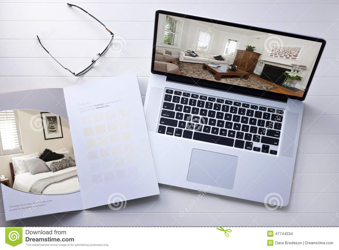 A still life with a laptop computer and paint sample brochure