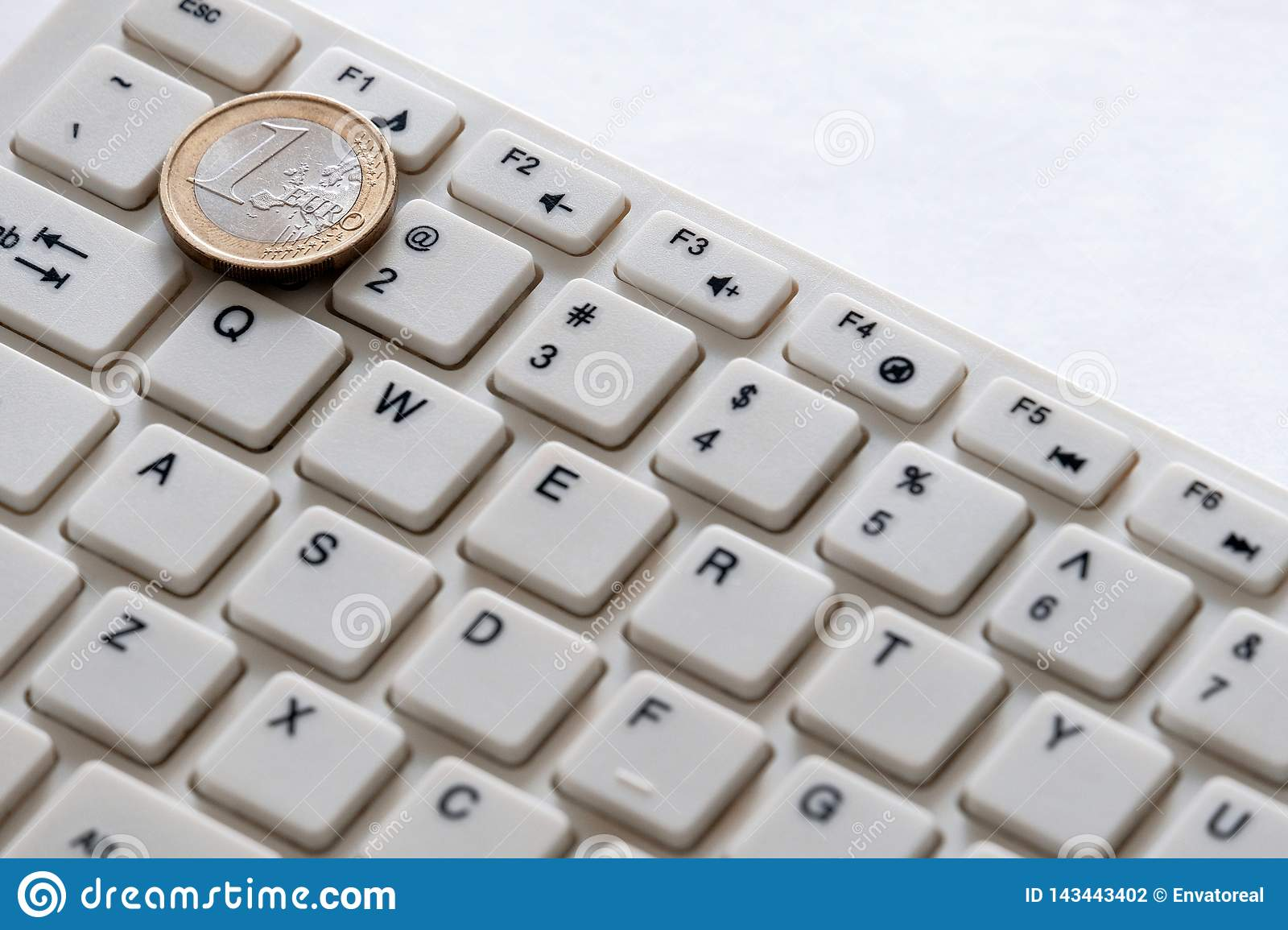 Computer keyboard and one euro coin close up on a white background. Internet business. Currency exchange
