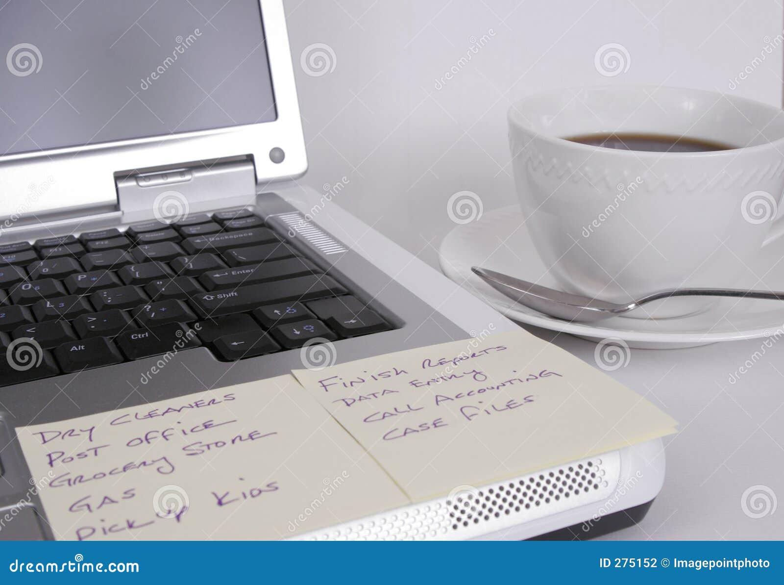 Computer met nota s en kop van koffie
