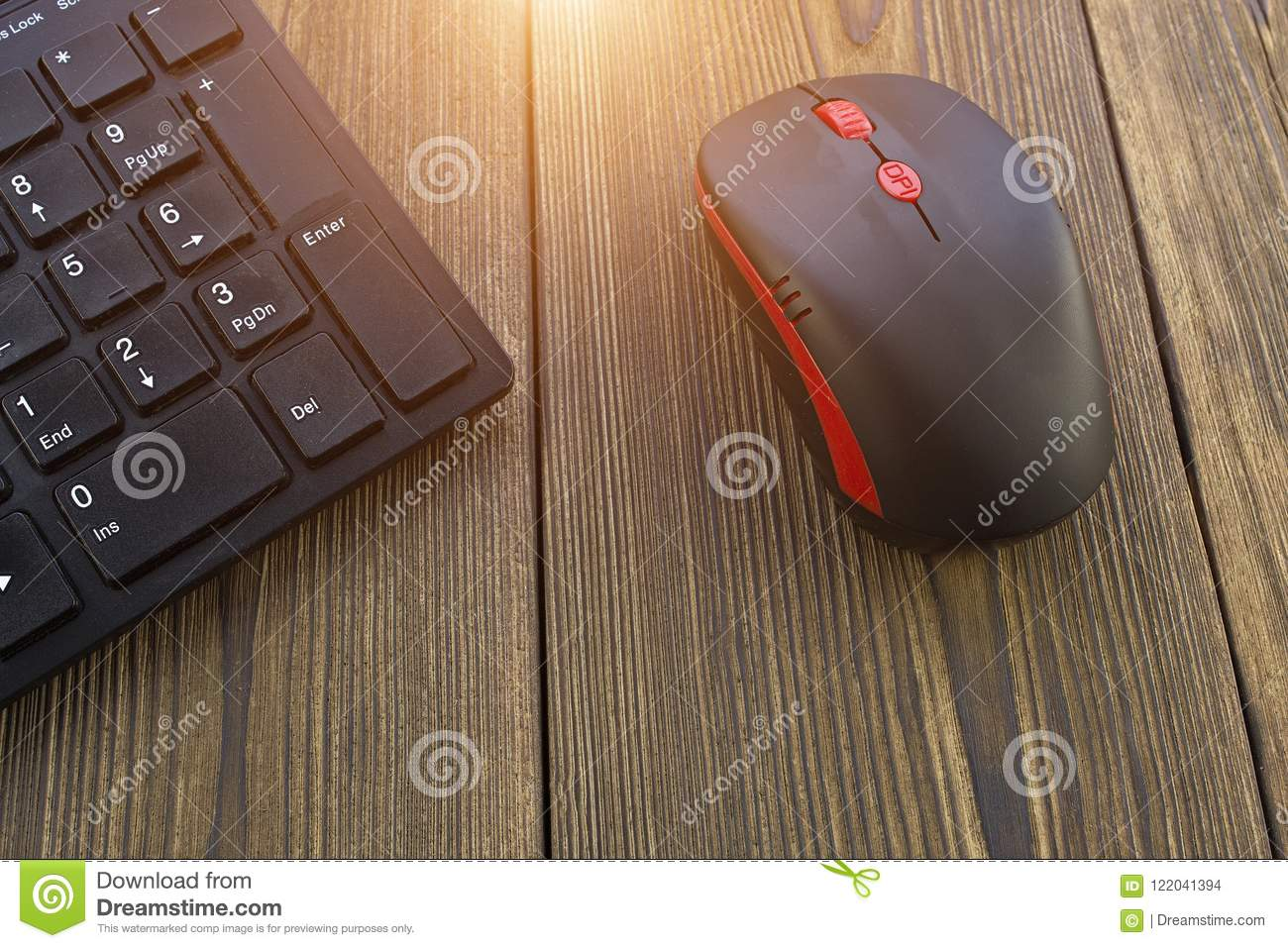 Computer mouse and keyboard on a wooden background, sun, close-up, keyboard