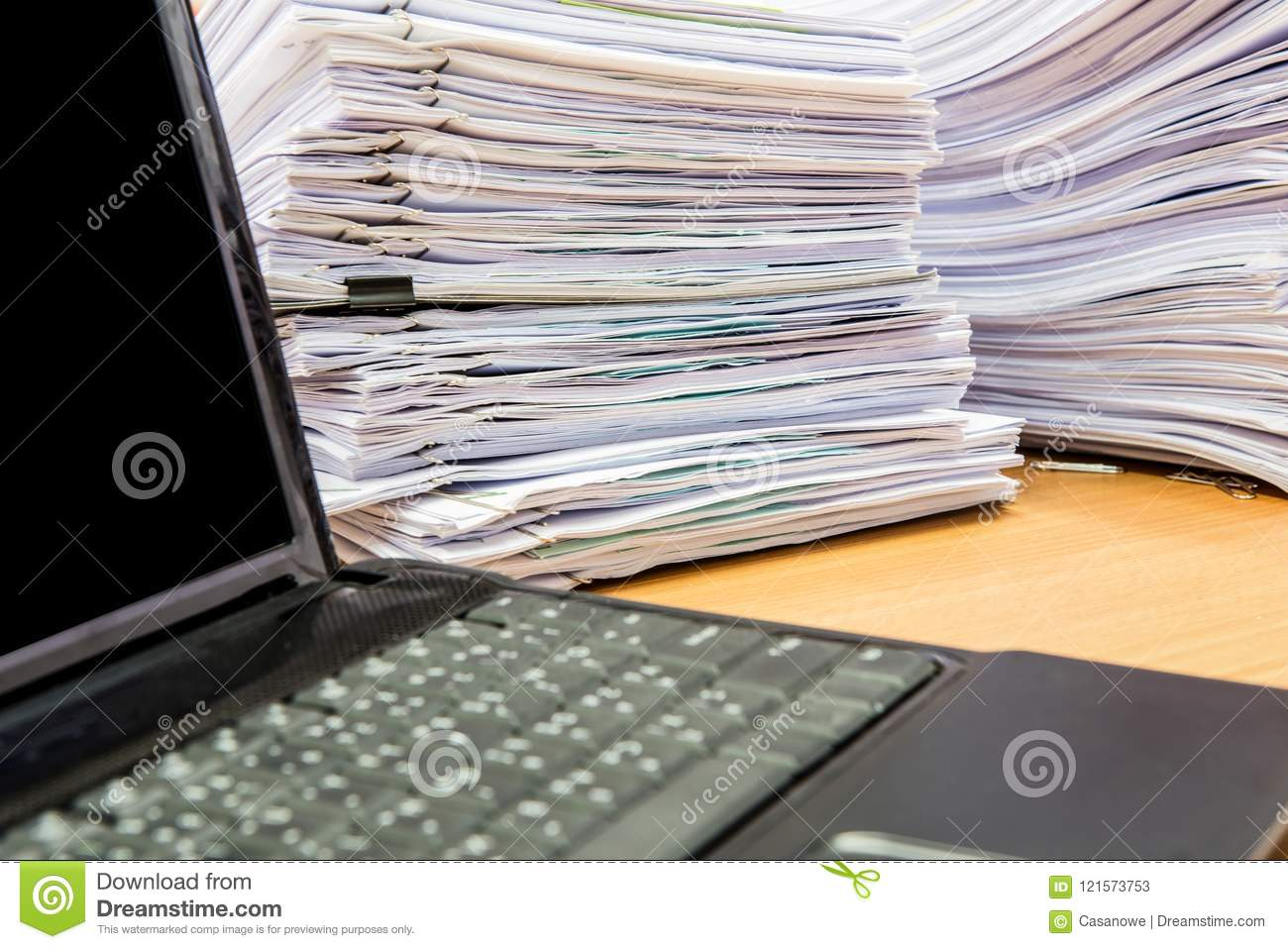 Computer Notebook And Documents On Desk Stack Up High