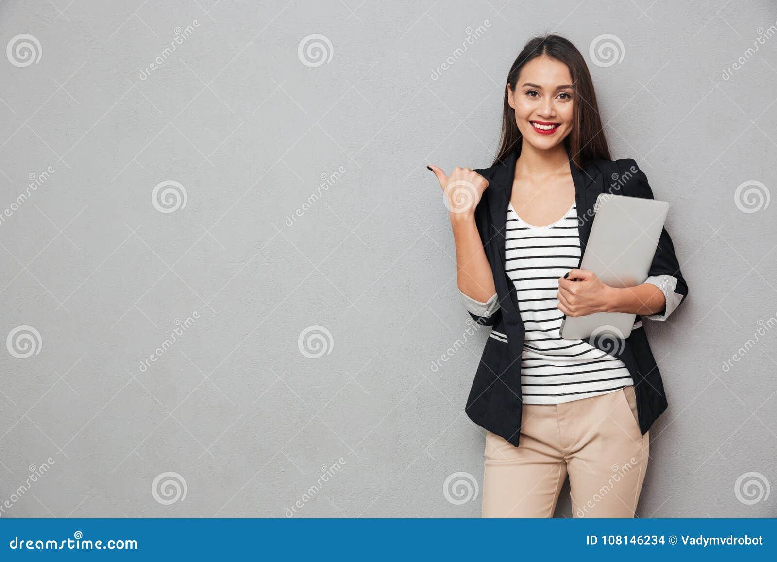 Computer portatile asiatico sorridente della tenuta della donna di affari ed indicare via