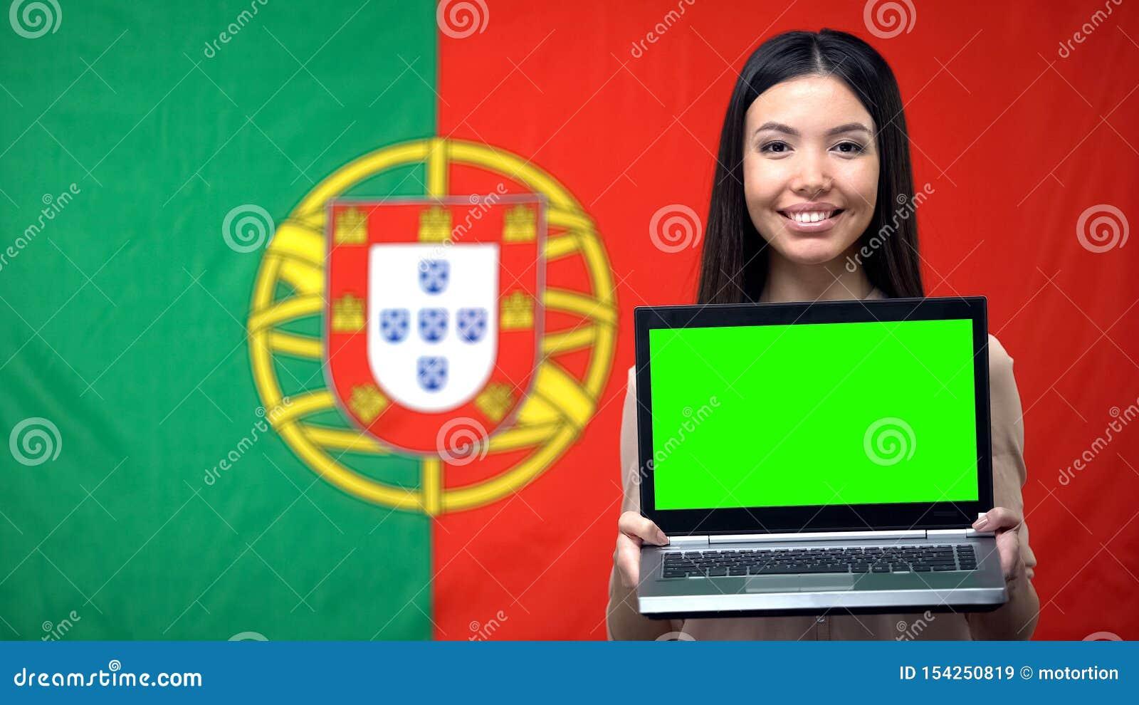 Computer portatile della tenuta della studentessa con lo schermo verde, bandiera portoghese su fondo