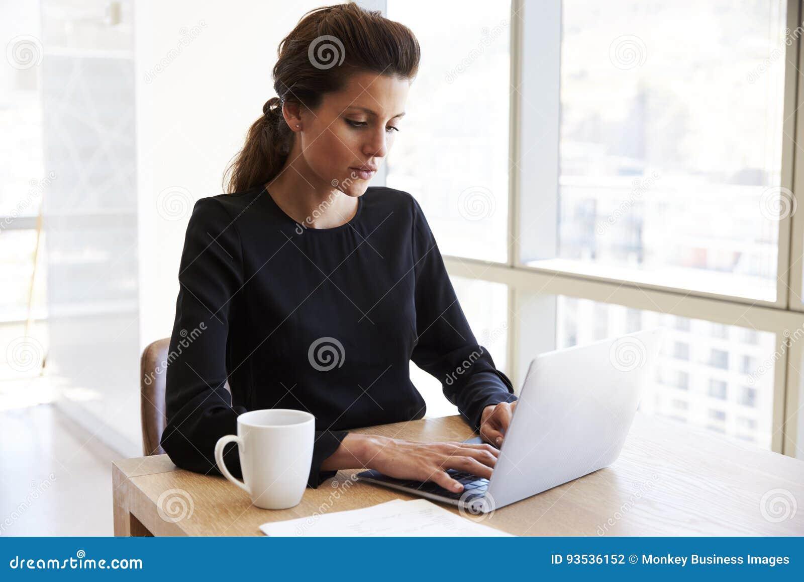 Computer portatile di Working Alone On della donna di affari nella sala del consiglio dell ufficio