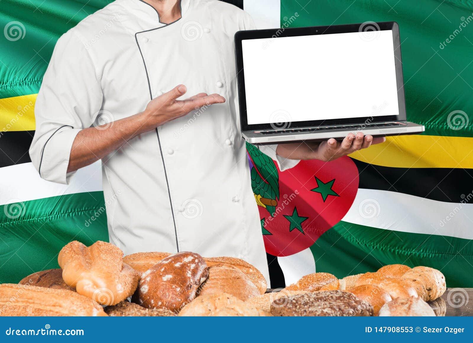 Computer portatile domenicano della tenuta del panettiere sulla bandiera della Dominica e sul fondo dei pani Uniforme d uso del c