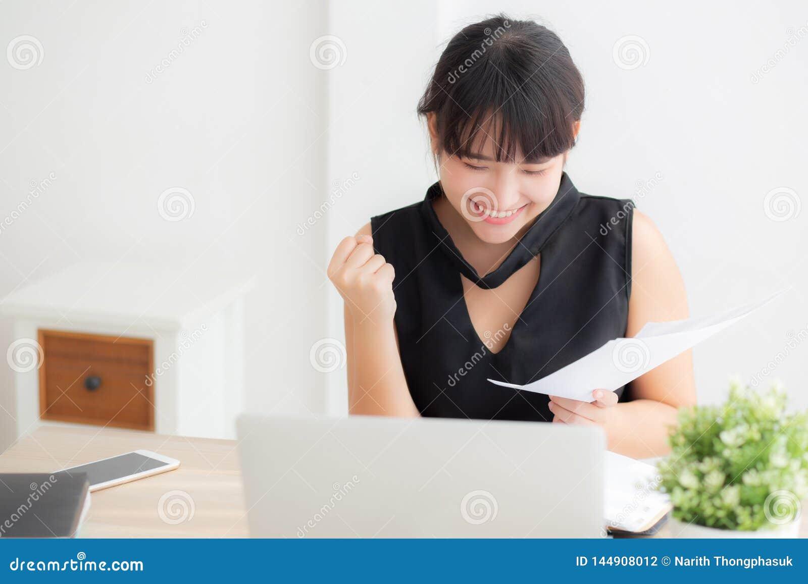 Computer portatile funzionante della bella giovane donna asiatica all ufficio, donna di affari che guarda i dati di statistica di