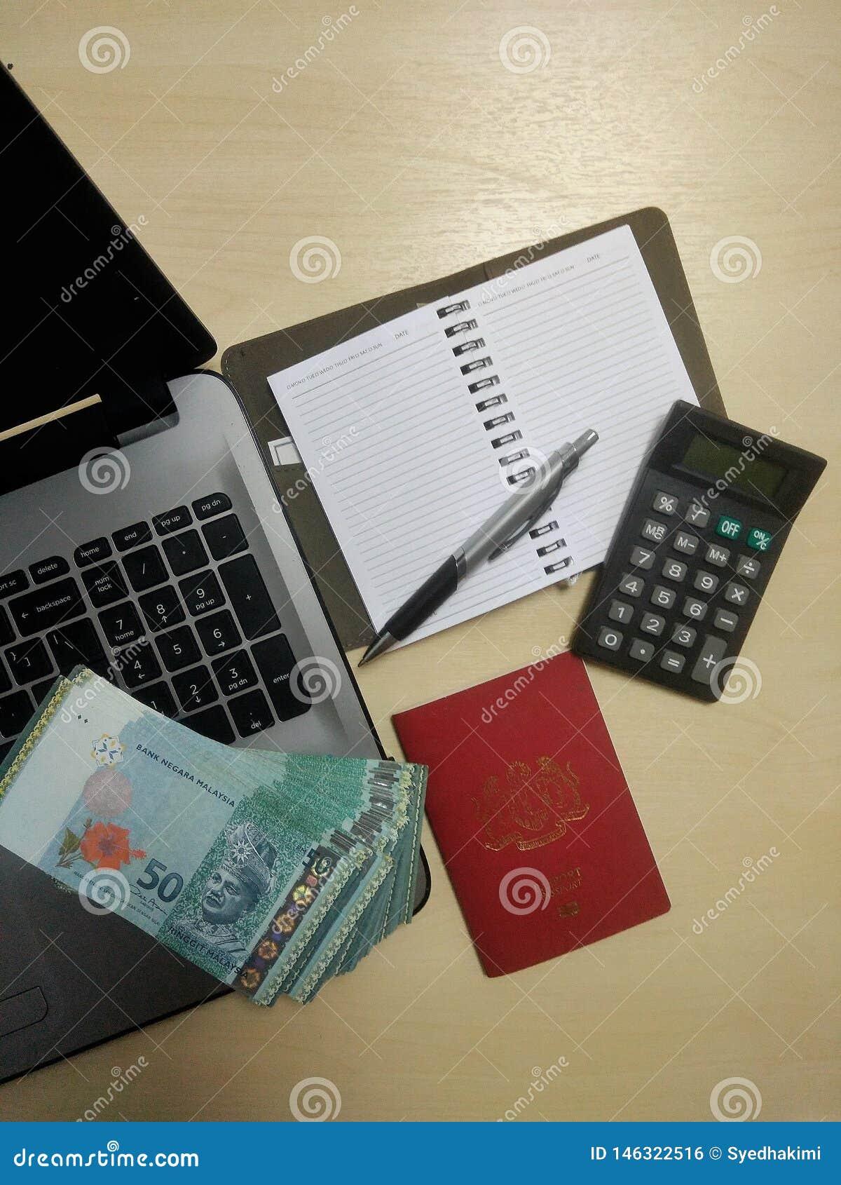 Computer portatile, soldi, passaporto, penna, calcolatore, scrittorio, taccuino con le pagine in bianco