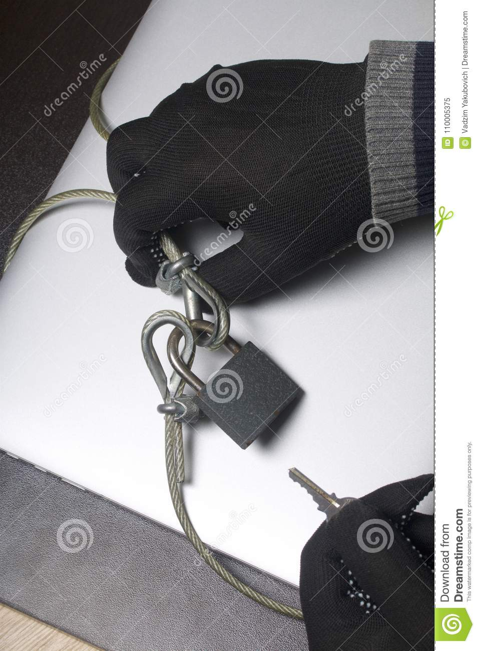 Computer security. Protection of access to data. The laptop is protected by a security cable and a lock. An attacker with gloves t