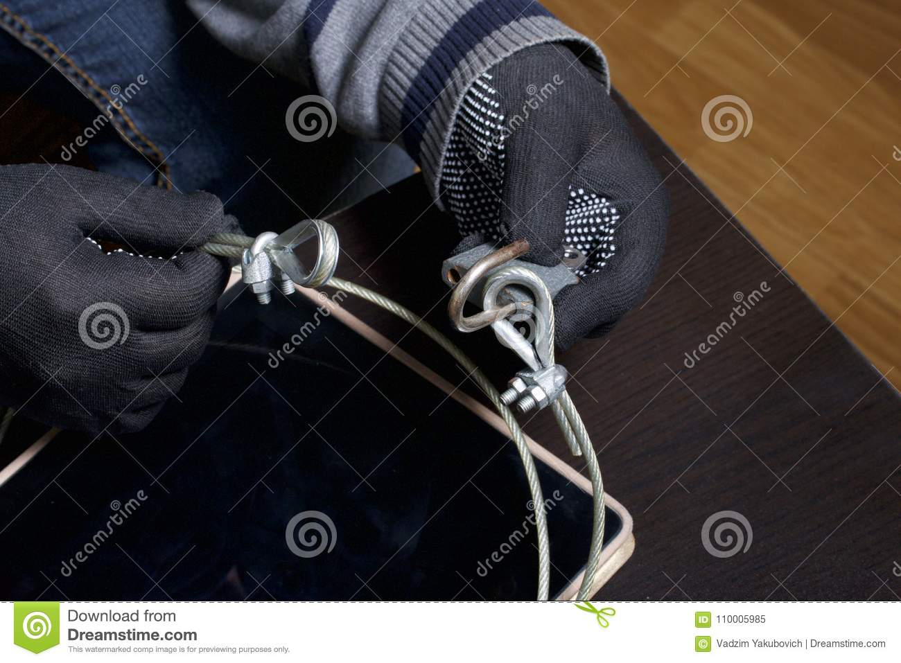 Computer security. Protection of access to data. The tablet is protected by a security cable and a lock. An attacker with gloves t
