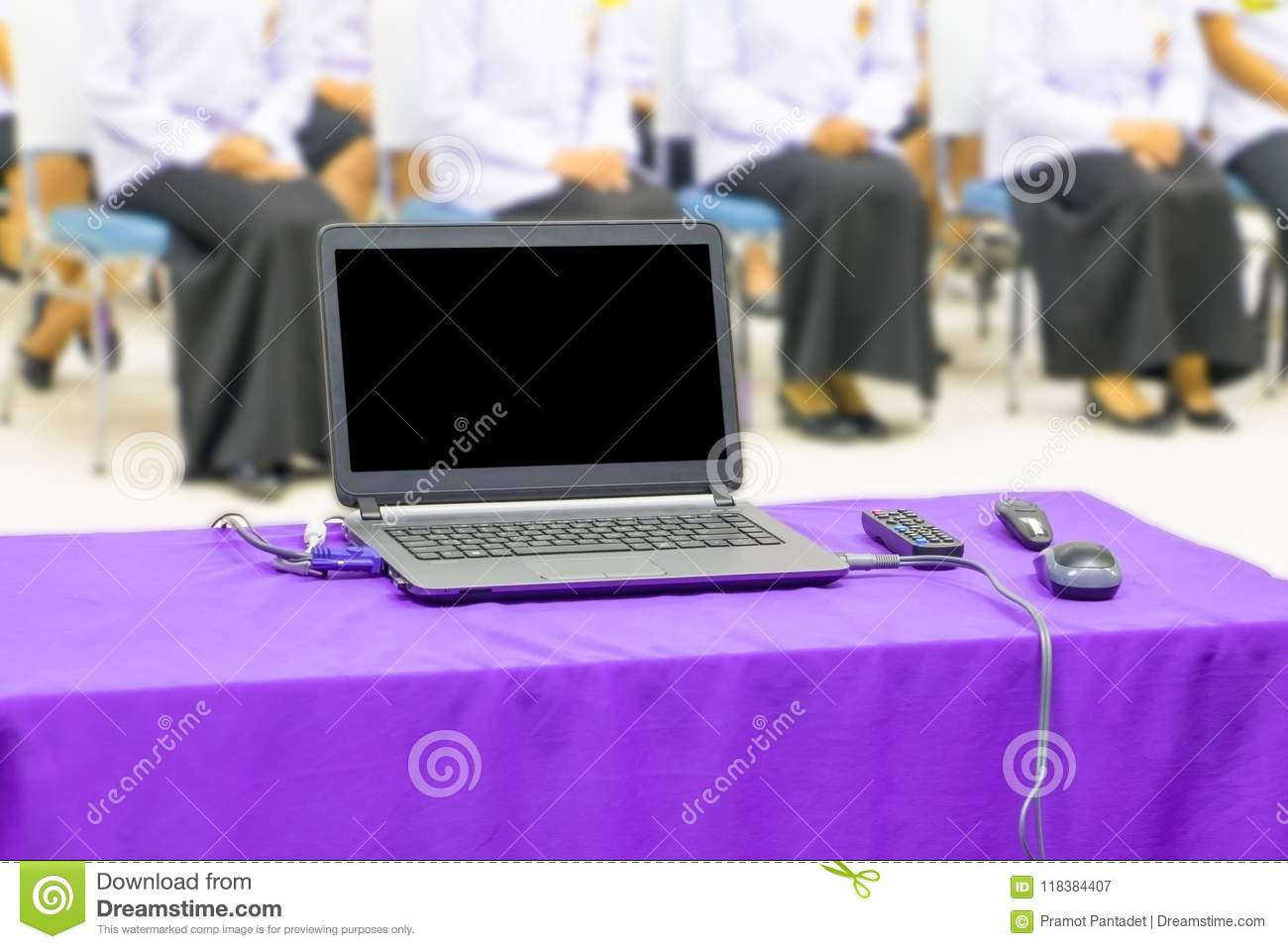 Computer on the table purple fabric and group students blur in the a classroom with copy space add text