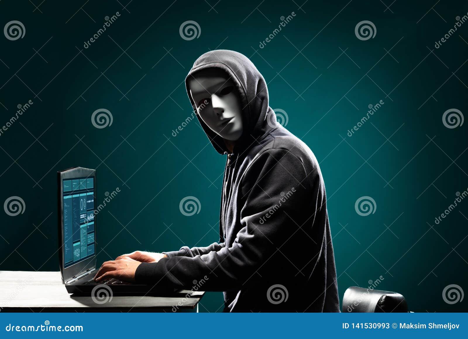 Computerhakker in wit masker en hoodie Verduisterd donker gezicht Gegevensdief, Internet-fraude, darknet en cyber veiligheid