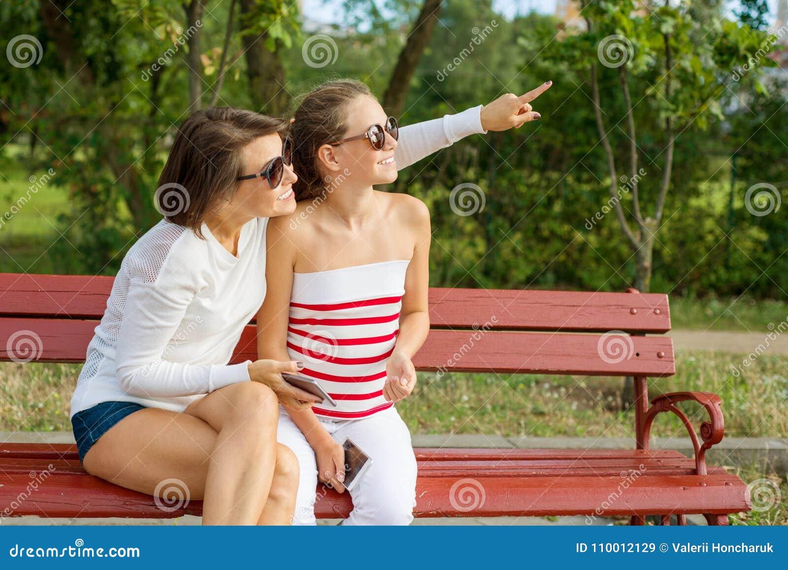 Comunicación entre el padre y el niño Adolescente de la mamá y de la hija que habla y que ríe mientras que se sienta en el banco