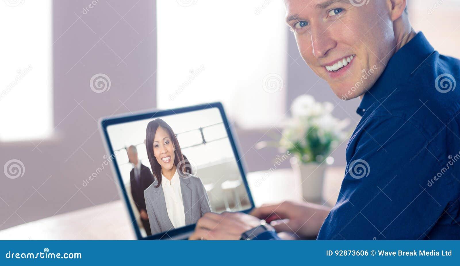 Comunicación video sonriente del hombre de negocios con el colega en el ordenador portátil en oficina