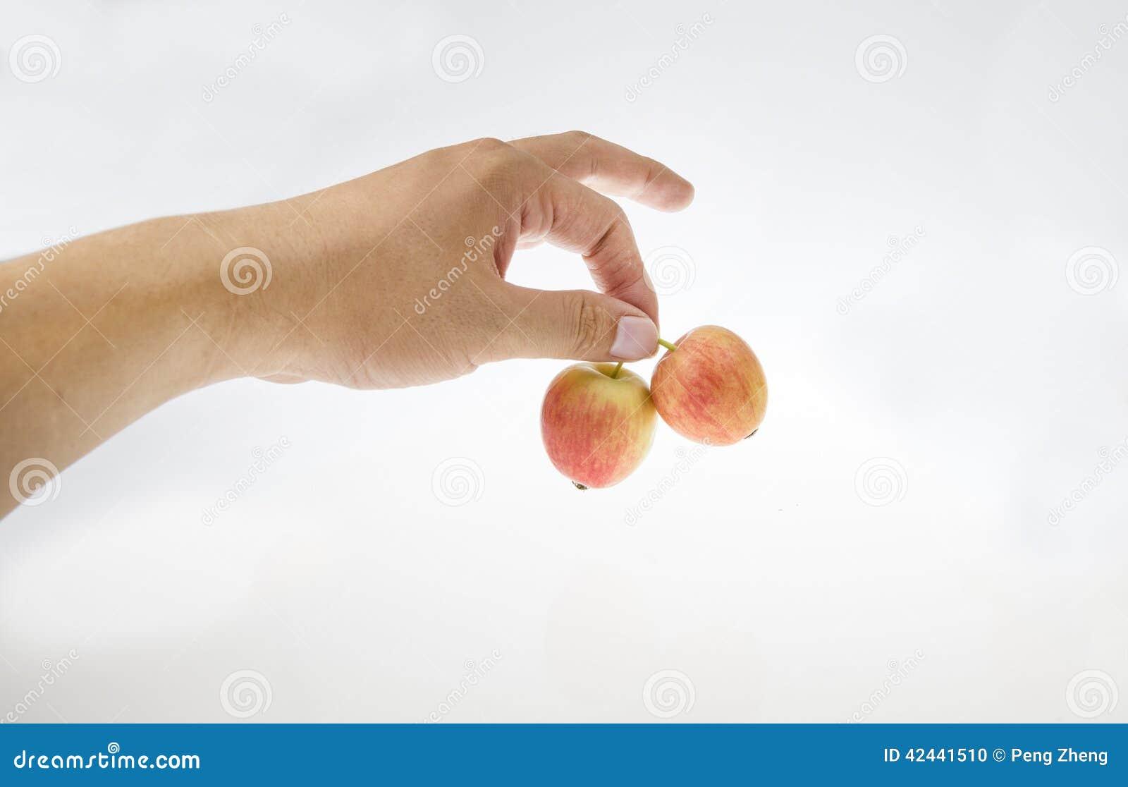 Con dos pequeñas manzanas en su mano