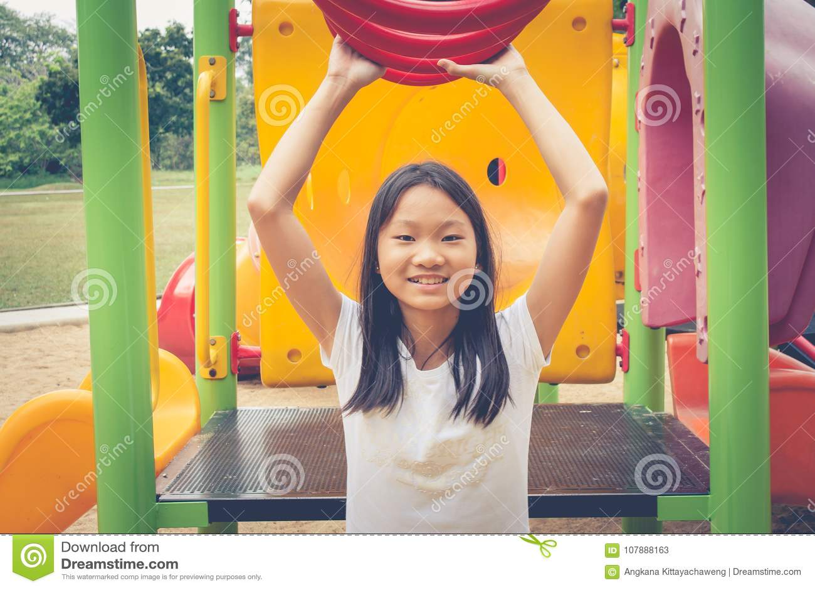 Conceito adorável e do feriado: Sentimento bonito da criança pequena engraçado e felicidade no campo de jogos