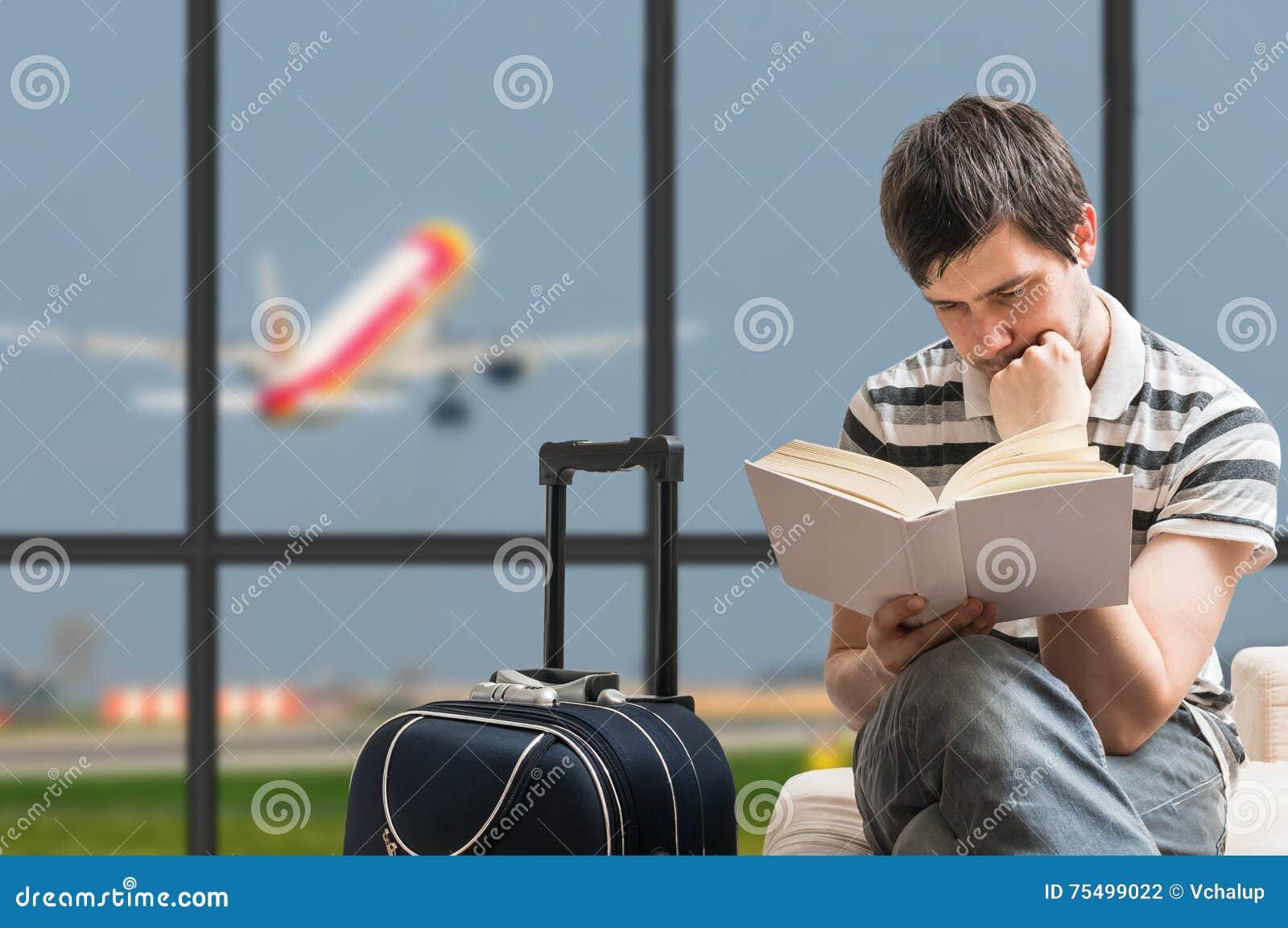 Conceito atrasado do avião O homem está sentando-se com bagagem no aeroporto