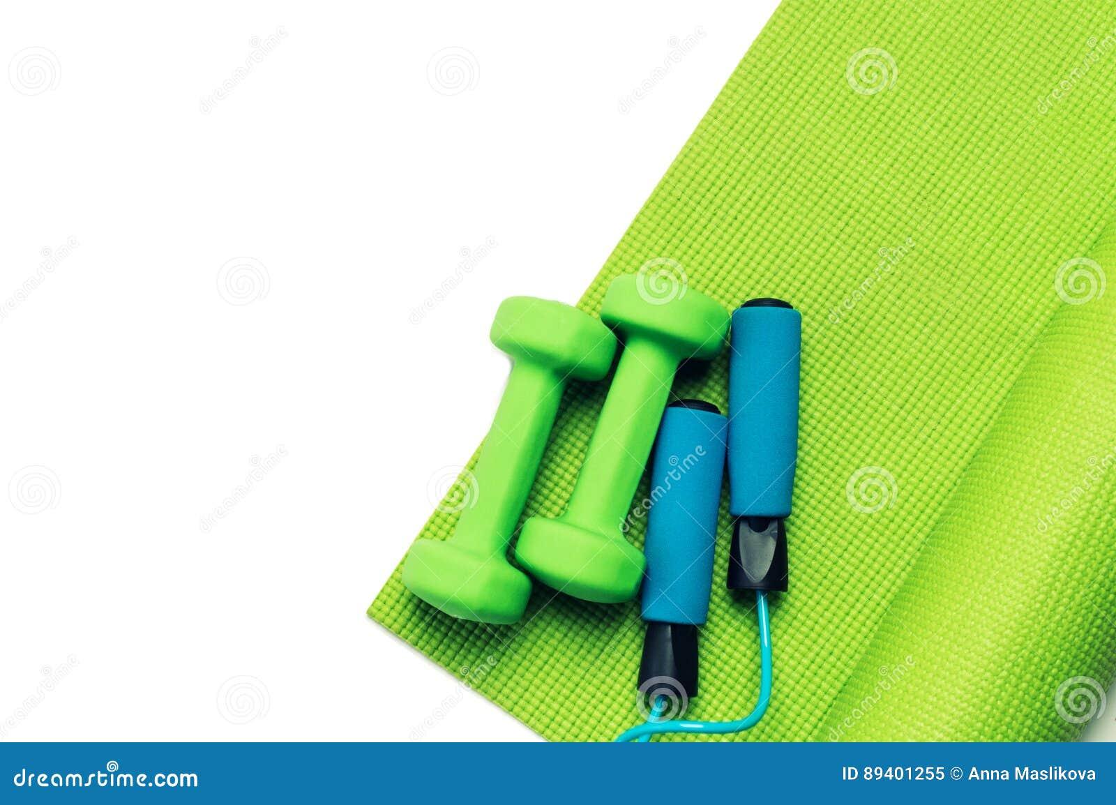 Conceito da aptidão - esteira da ioga, pesos e corda de salto verdes