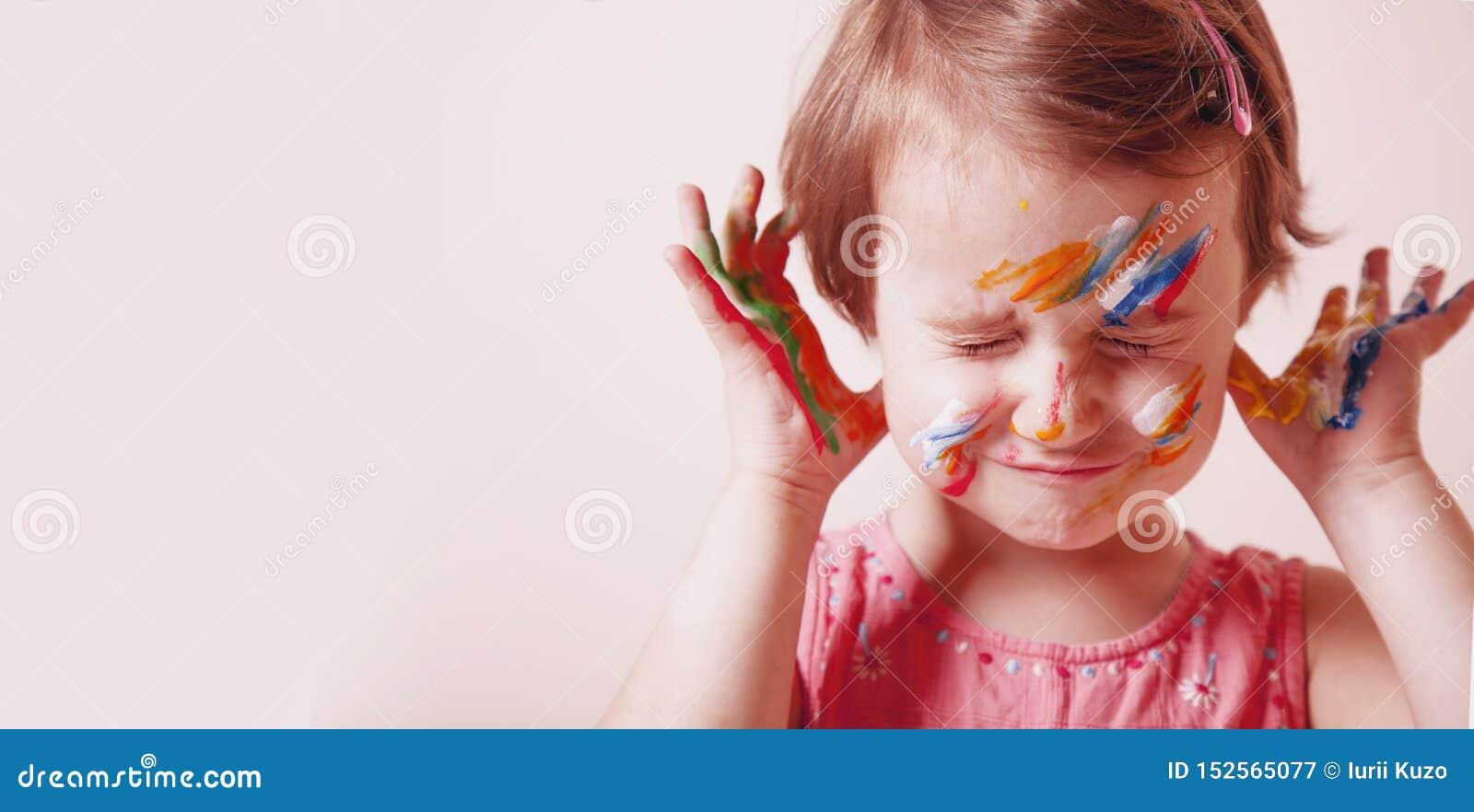 Conceito da arte, o criativo e da felicidade da inf?ncia Mãos e cara pintadas coloridas em uma menina bonita da criança pequena
