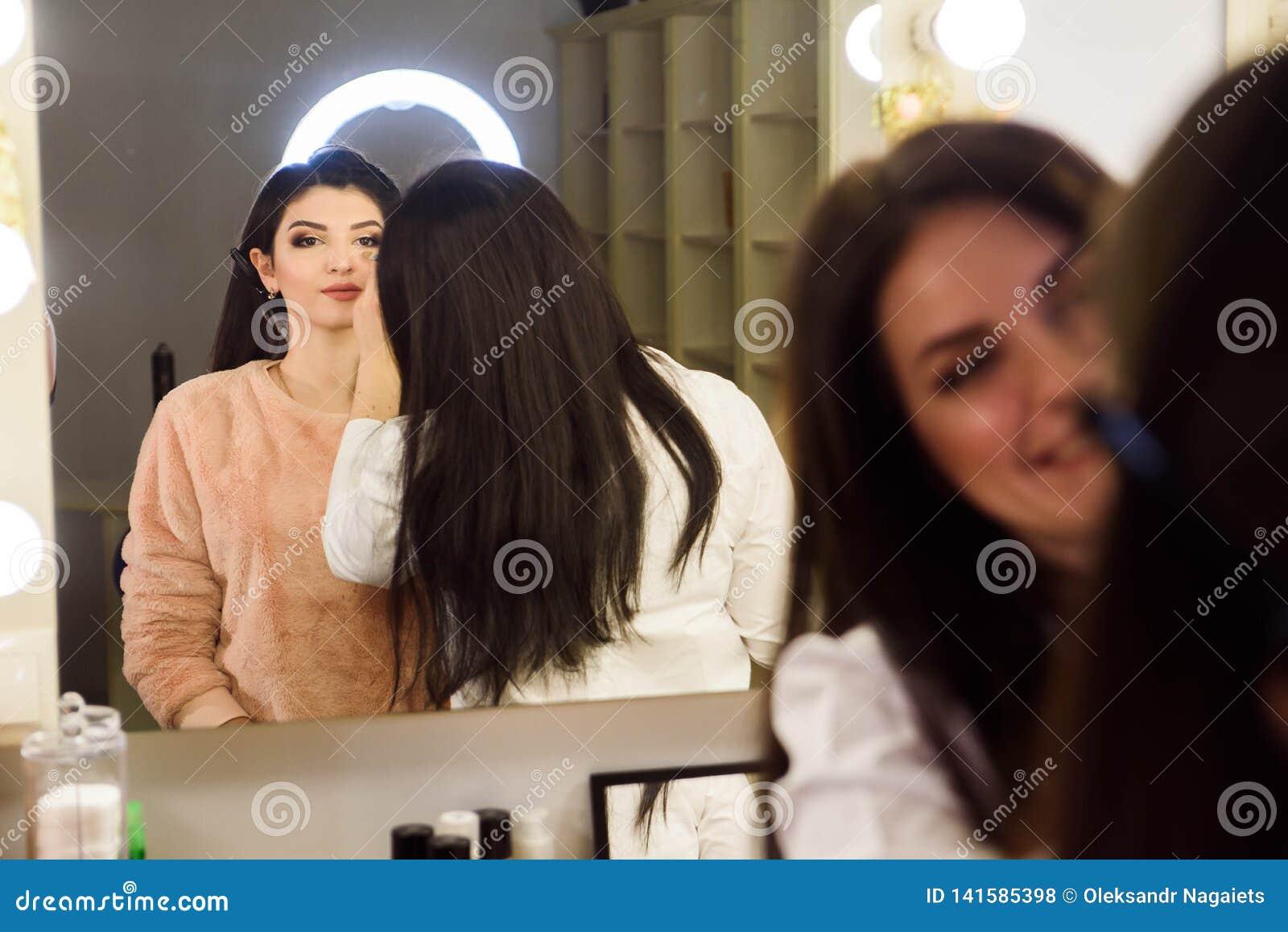 Conceito da cara Feche acima da mulher que obter compõe nas pálpebras Aplicando a sombra com a escova pelo artista profissional