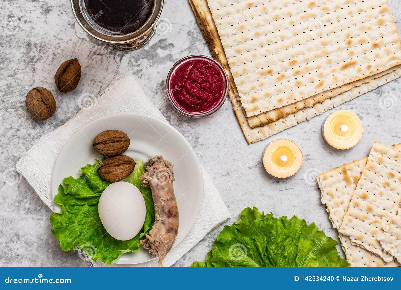 Conceito da celebra??o de Pesah Fundo da p?scoa judaica com a placa do vinho, do matza e do seder no cinza Vista superior Com esp