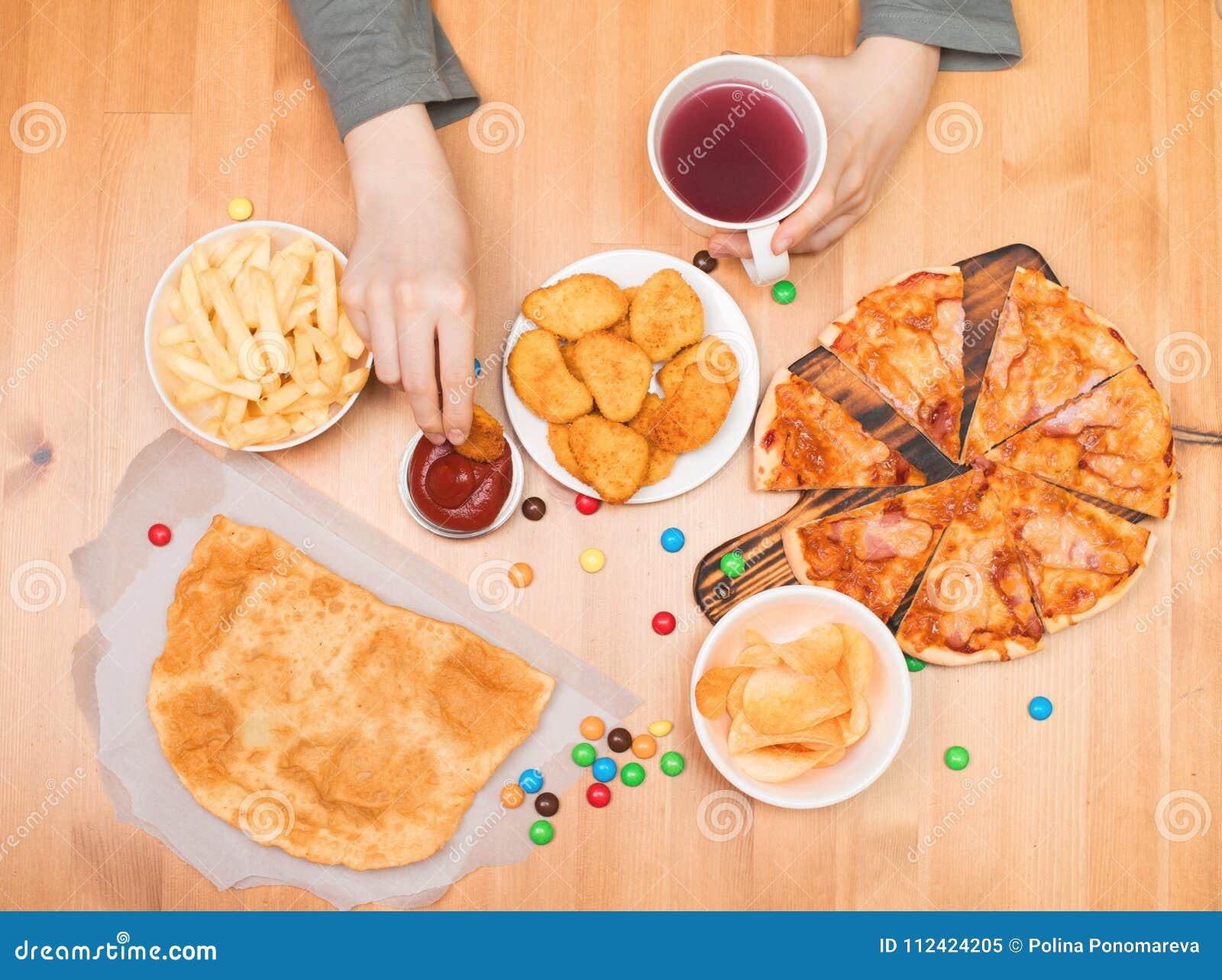 Conceito da comida lixo do fast food Menino adolescente que come pepitas, pizza, qui