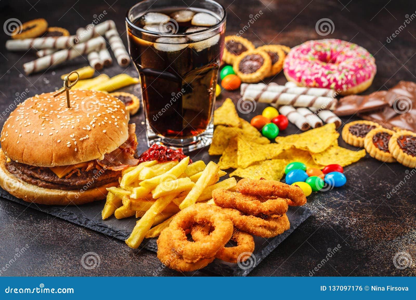 Conceito da comida lixo Fundo insalubre do alimento Fast food e açúcar Hamburguer, doces, microplaquetas, chocolate, anéis de esp