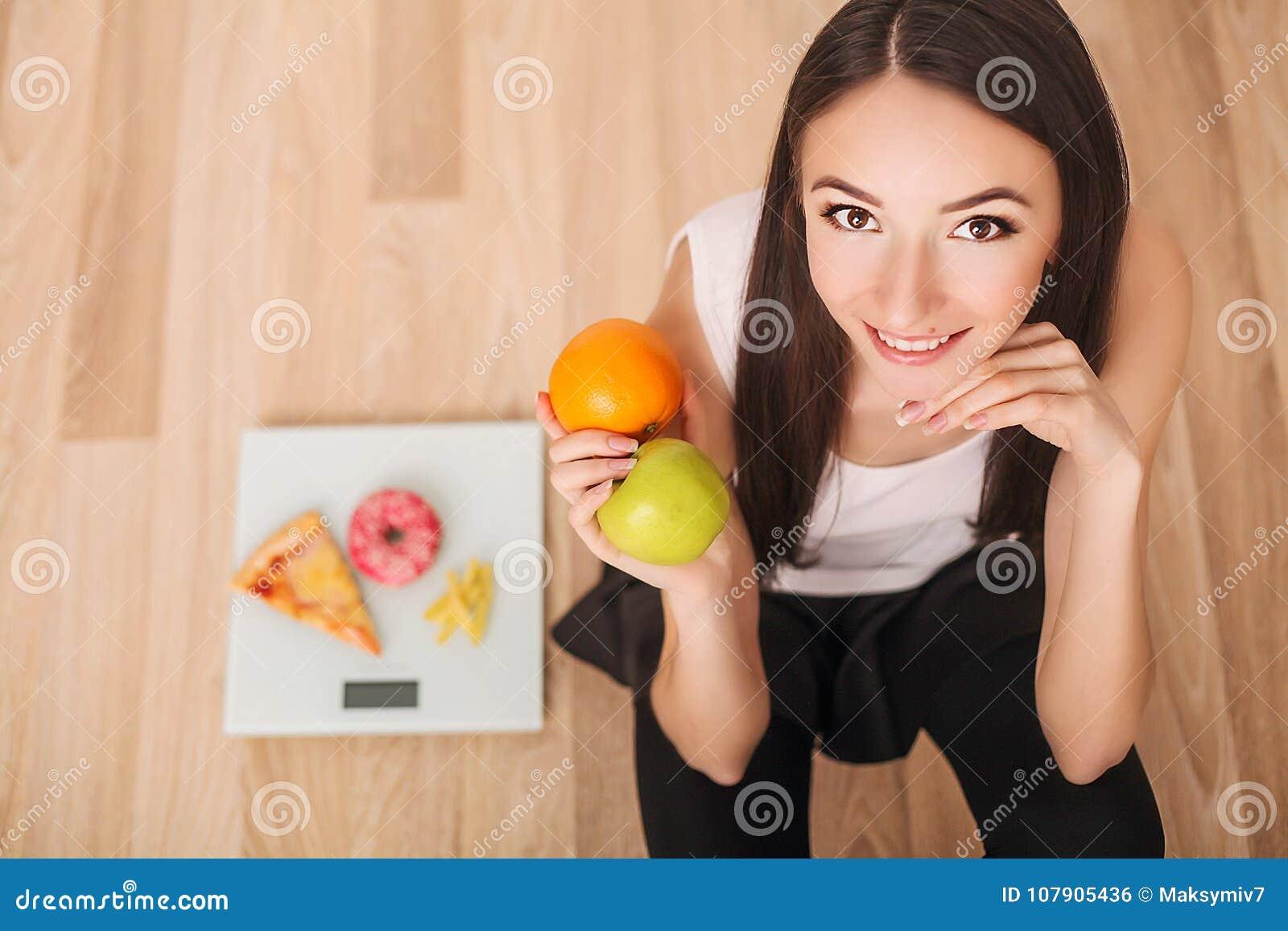 Conceito da dieta e do fast food Mulher excesso de peso que está na escala de peso que guarda a pizza Comida lixo insalubre Dieta