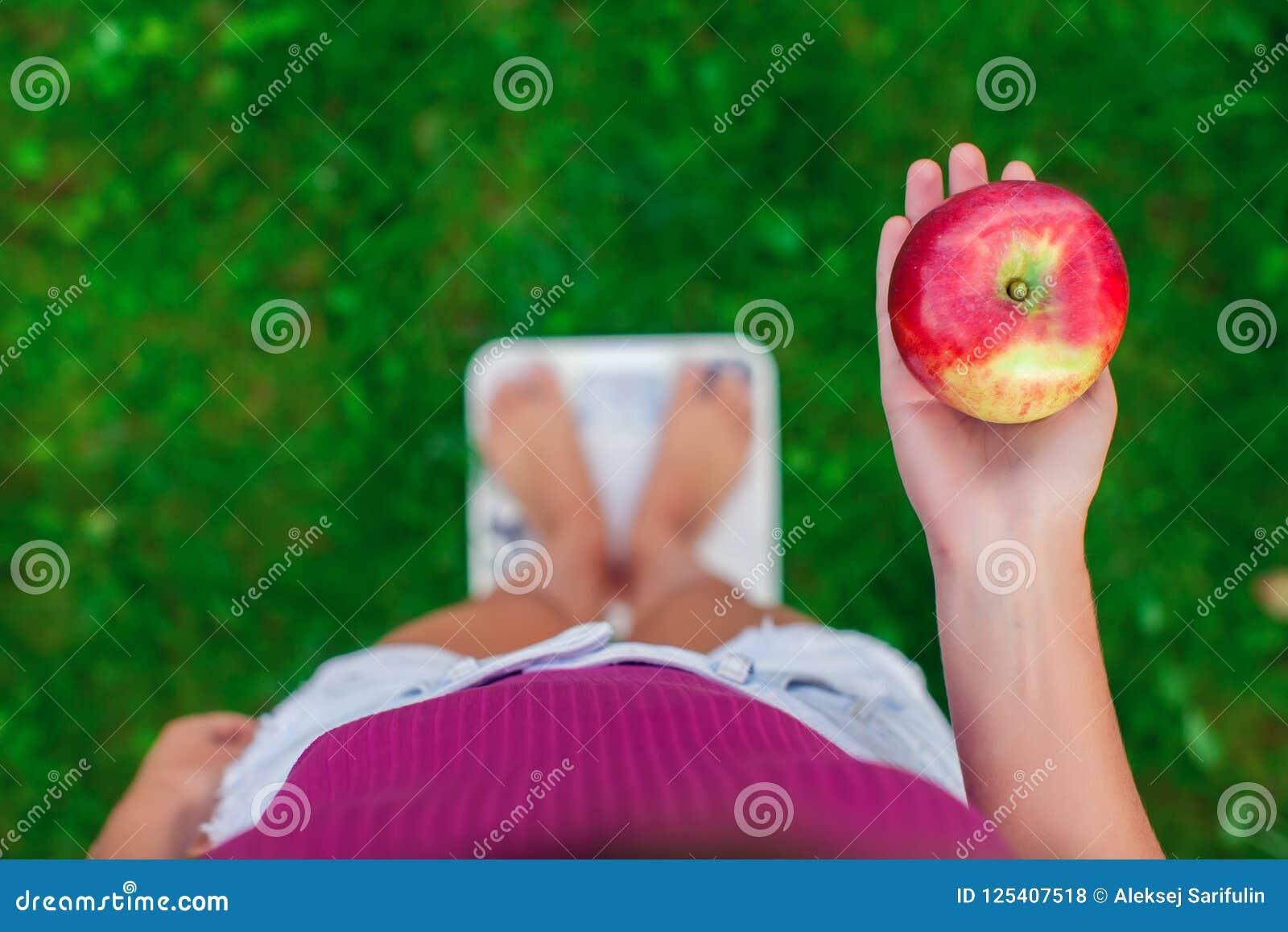 Conceito da dieta e do peso Jovem mulher que está em uma escala com