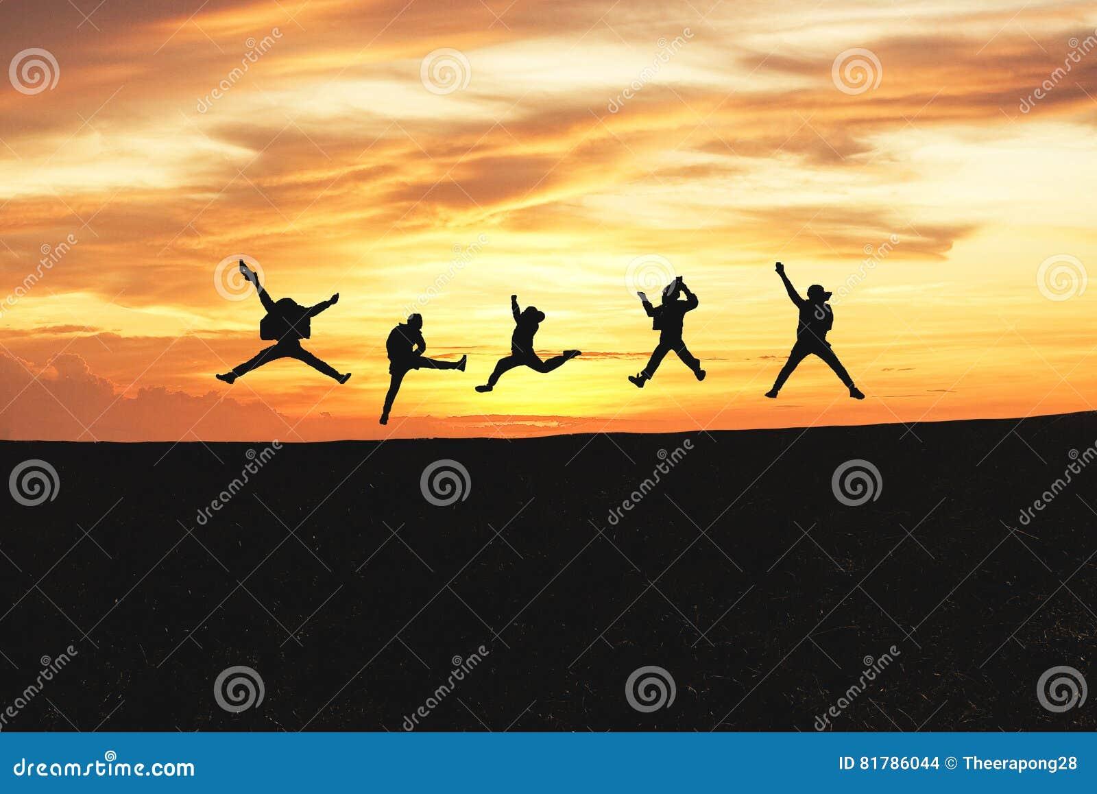 Conceito da emoção Silhueta de um grupo de pessoas feliz que salta no por do sol na montanha
