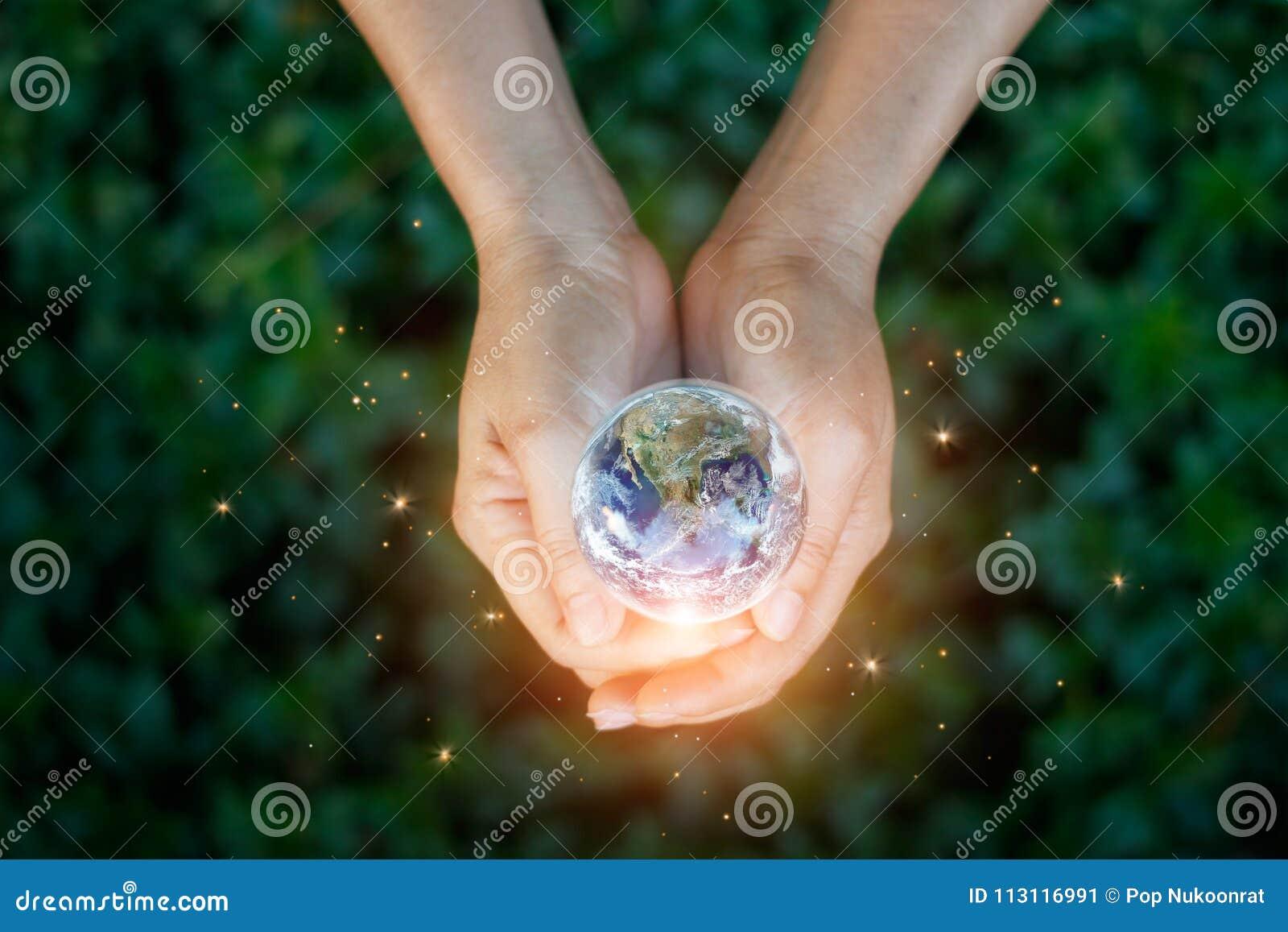 Conceito da energia da economia, mão que mantém a terra contra a natureza