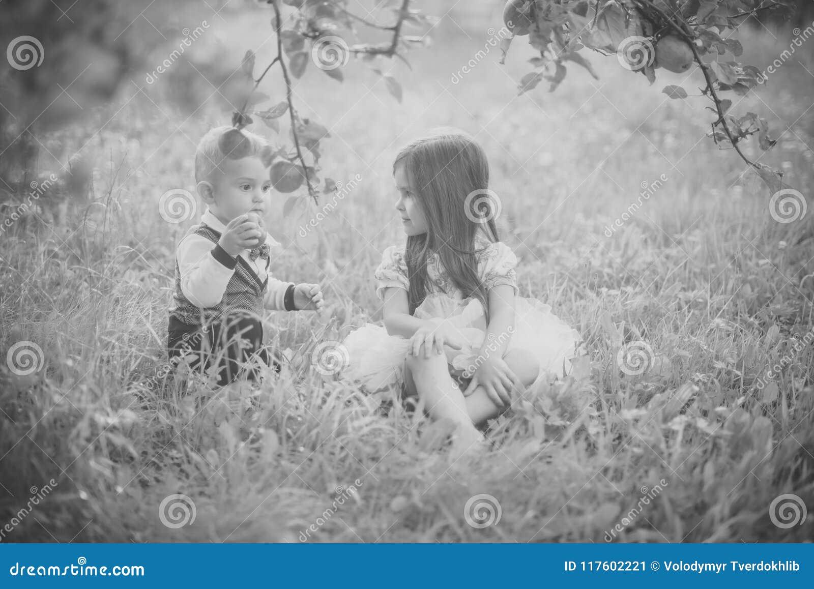 Conceito da felicidade das crianças da infância da criança As crianças sentam-se sob a árvore de maçã no parque do verão