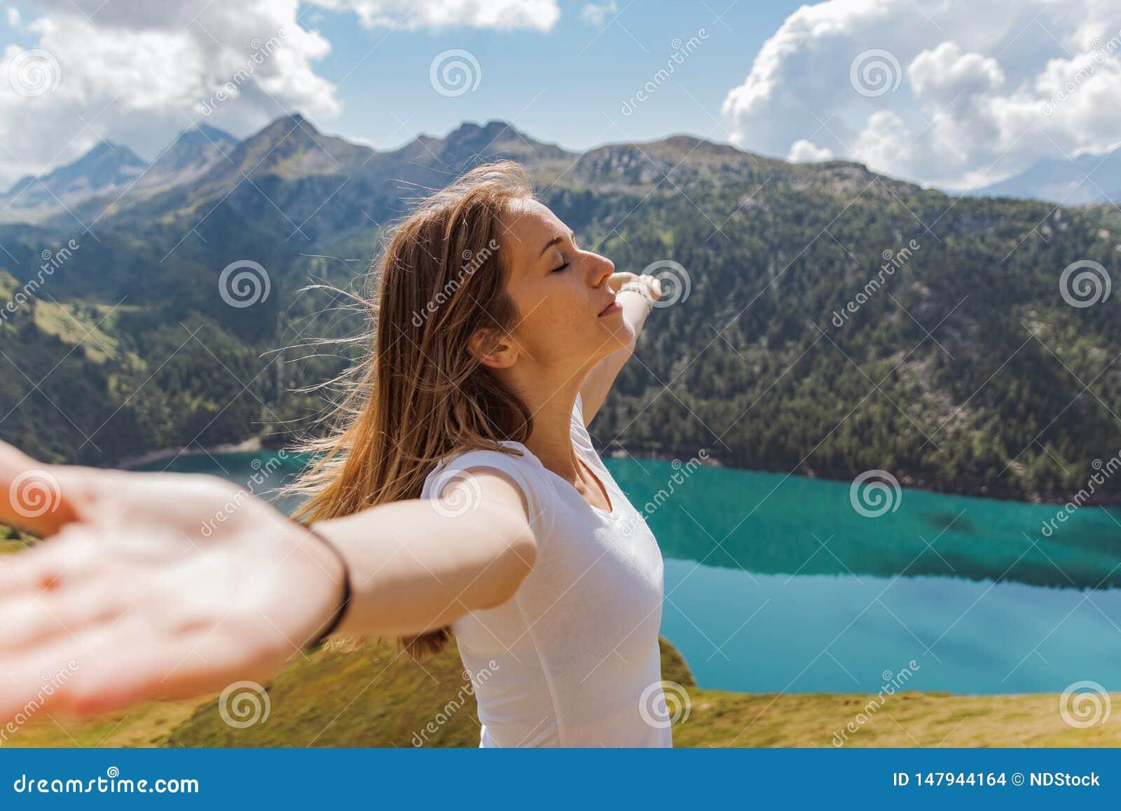 Conceito da liberdade de uma jovem mulher com seus braços aumentados apreciando o ar fresco e o sol