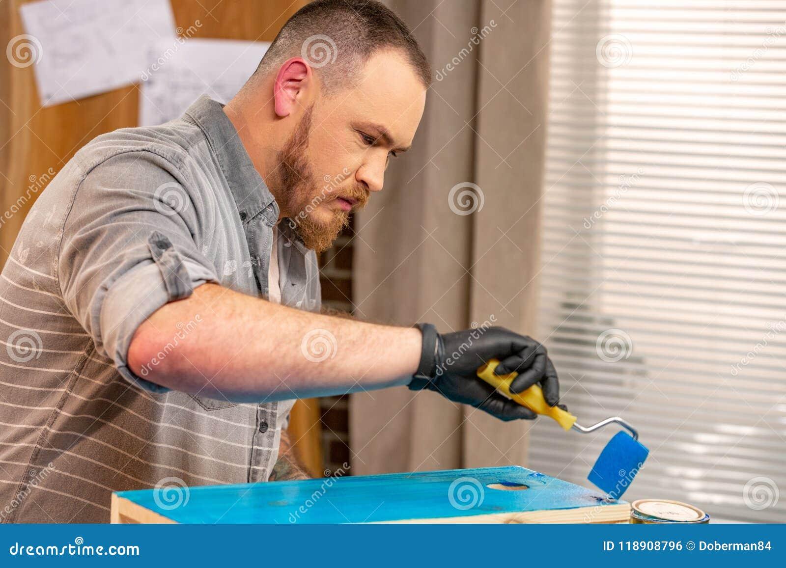 Conceito da profissão, da carpintaria, da carpintaria e dos povos - carpinteiro que trabalha com prancha e tampas de madeira ele