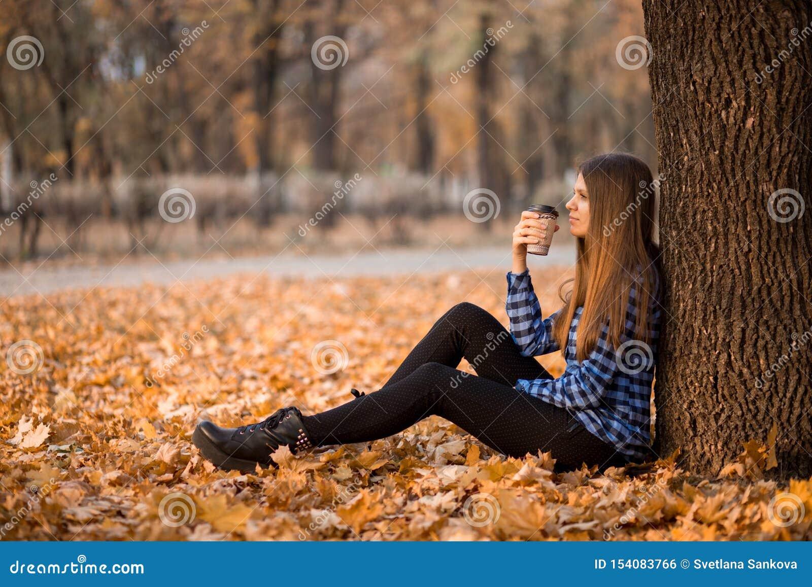 Conceito da queda Café bebendo da mulher feliz e alegre ao sentar-se nas folhas do parque sob a folhagem de outono