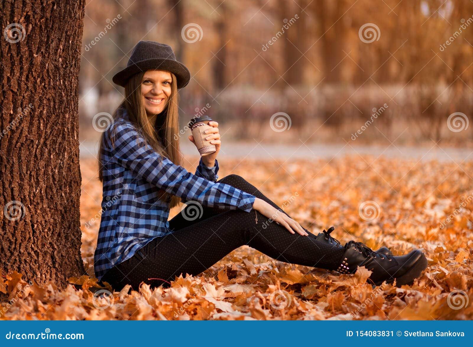 Conceito da queda Mulher feliz e alegre no chapéu, café bebendo ao sentar-se nas folhas do parque