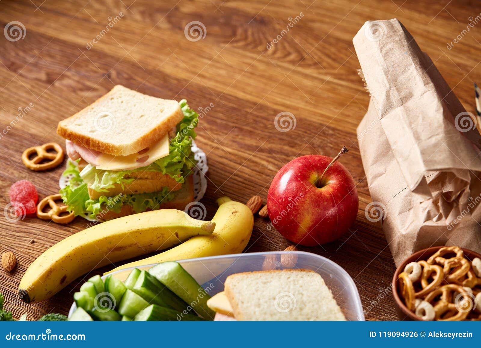 Conceito da ruptura do almoço escolar com fontes saudáveis da lancheira e de escola na mesa de madeira, foco seletivo