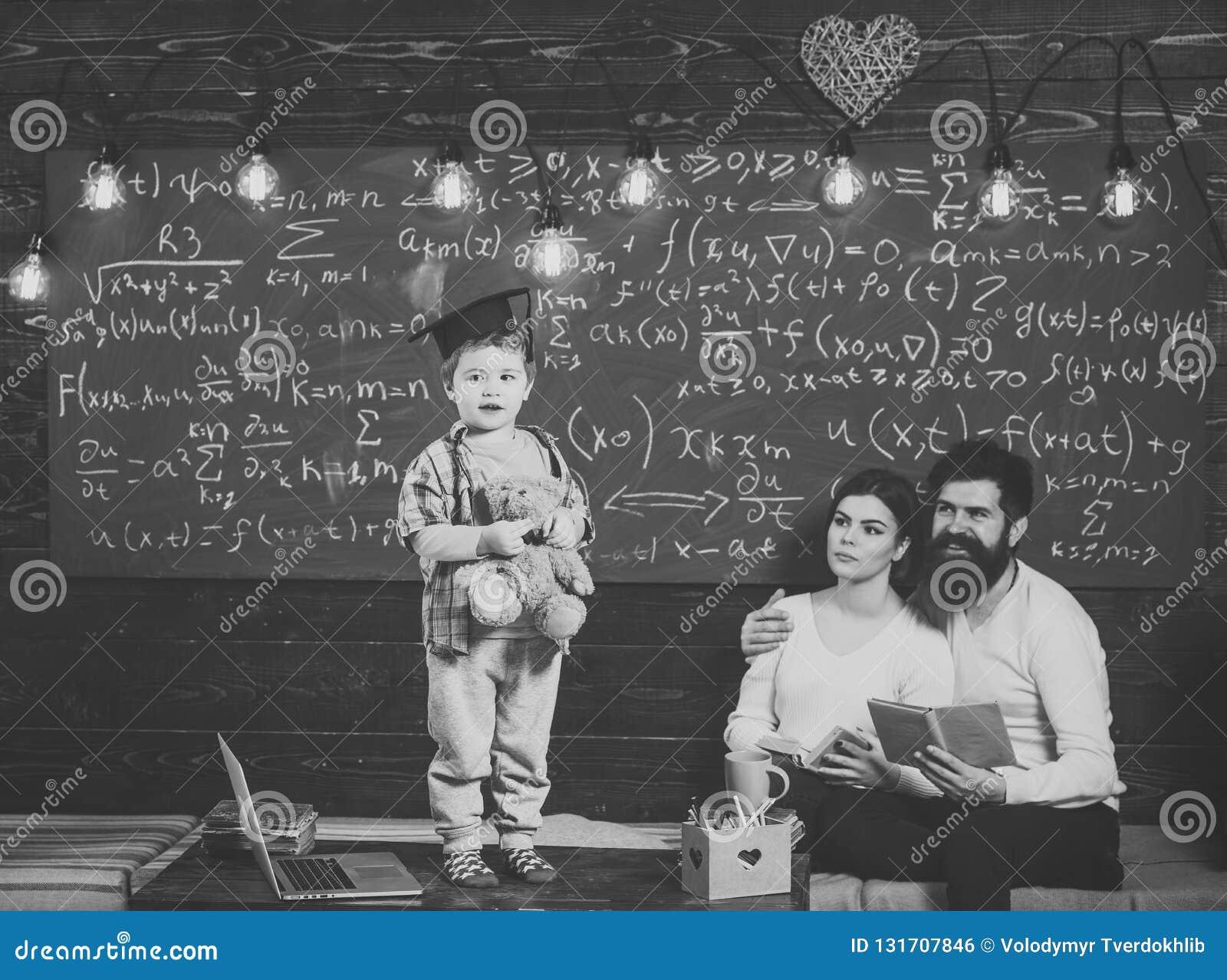 Conceito da sustentação A criança guarda o urso e a execução de peluche Menino que apresenta seu conhecimento à mamã e ao paizinh