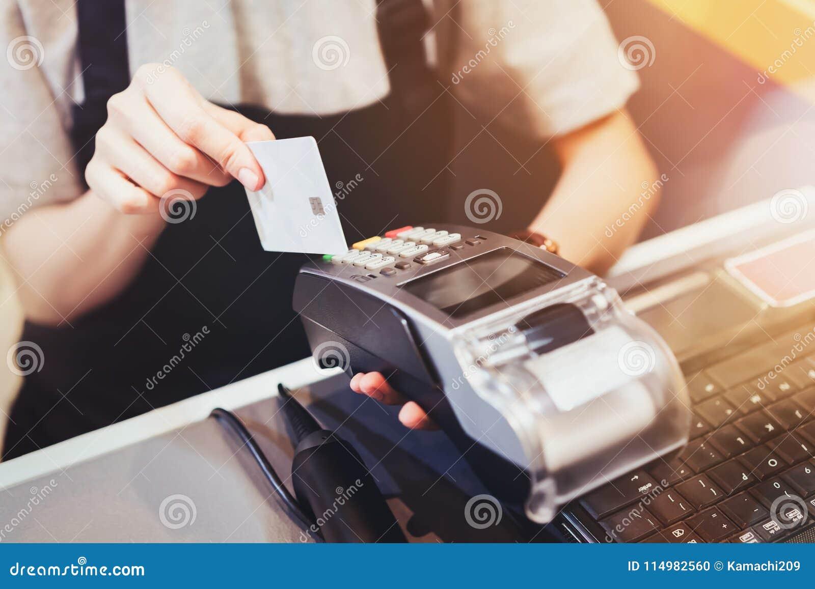 Conceito da tecnologia na compra sem usar o dinheiro Fim acima do cartão de crédito do uso da mão que swiping a máquina para paga