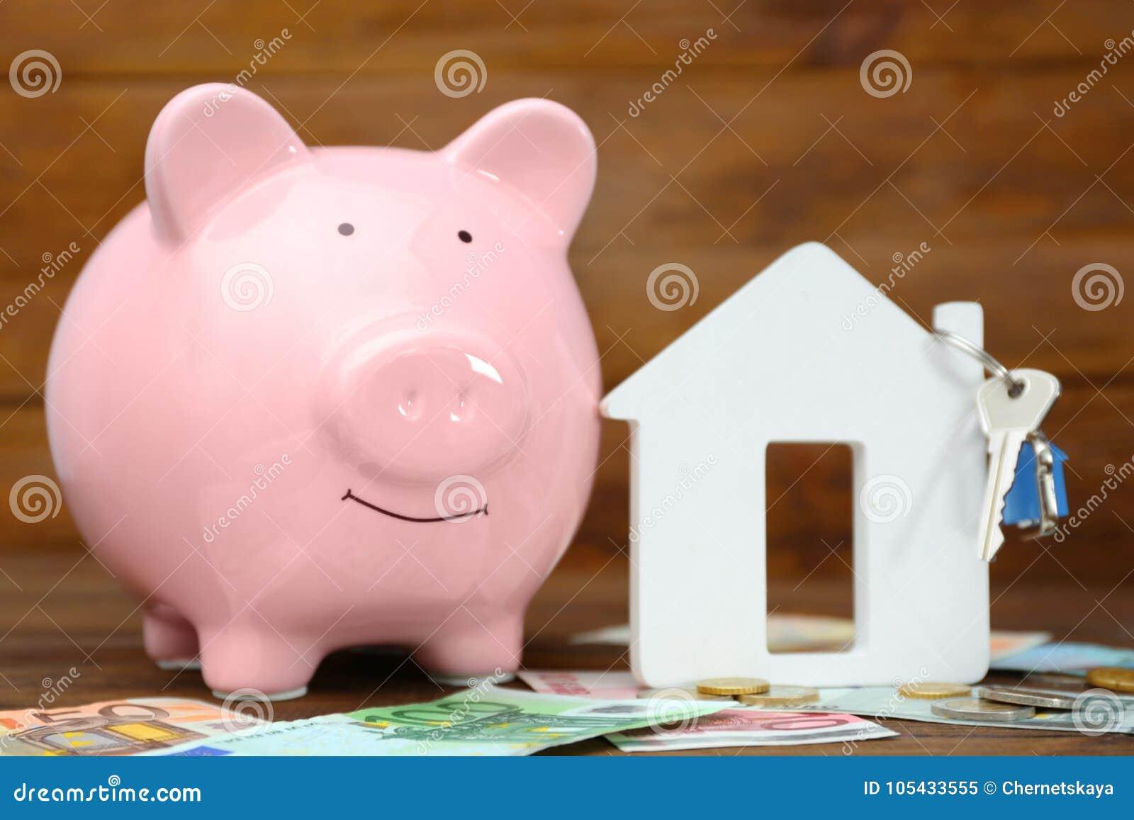 Conceito das economias Mealheiro com figura do dinheiro e da casa