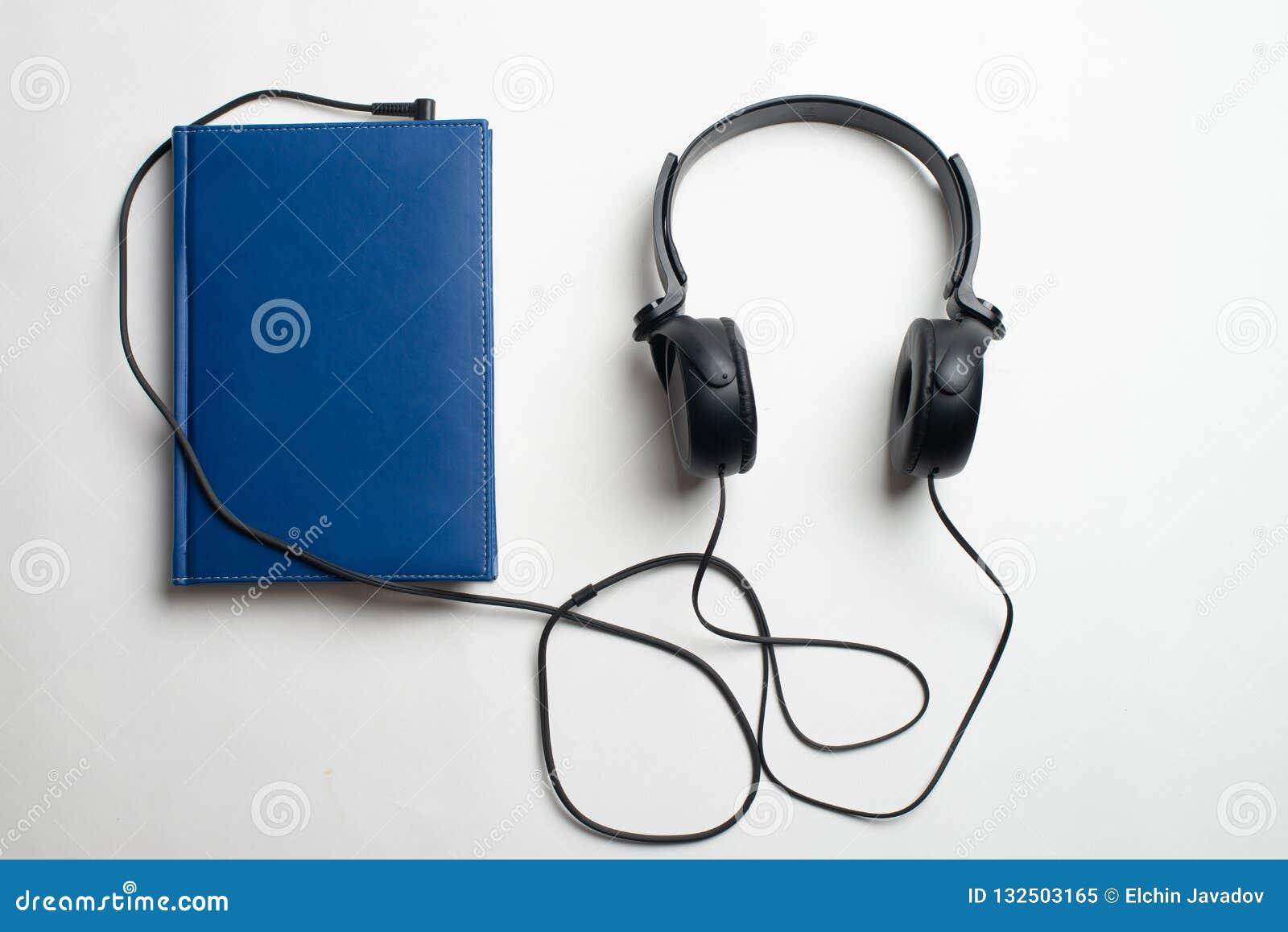 Conceito de Audiobook dos fones de ouvido e dos livros, fones de ouvido com livros