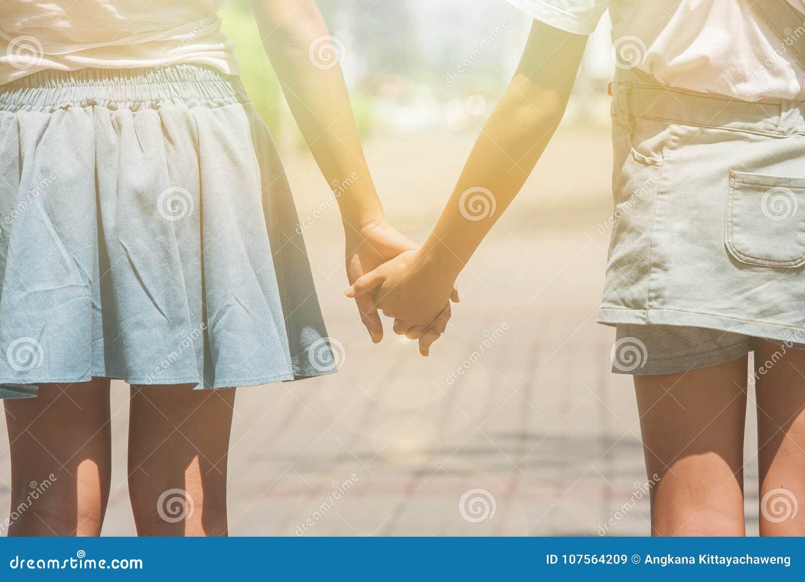 Conceito de família adorável: Duas irmãs que andam na passagem no parque público e que mantêm a mão unida