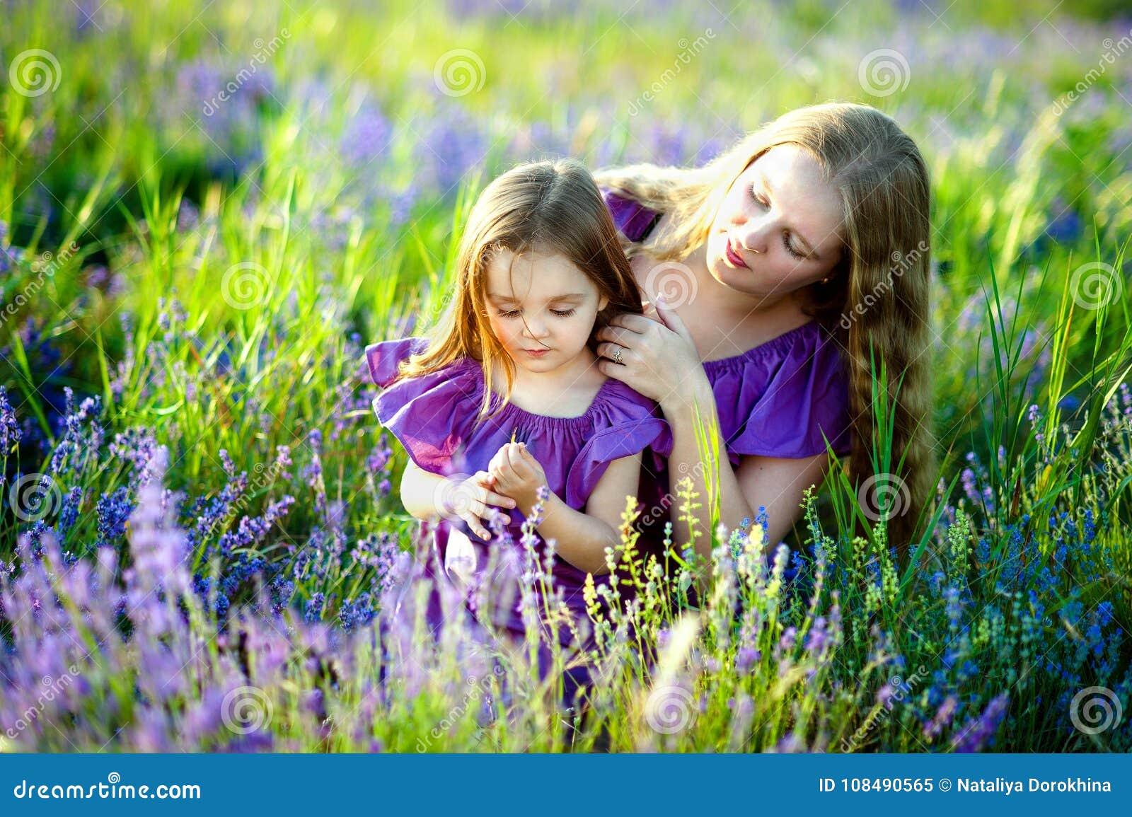 Conceito de família saudável feliz Uma mulher bonita nova com sua filha bonito pequena que anda no campo do ouro do trigo na