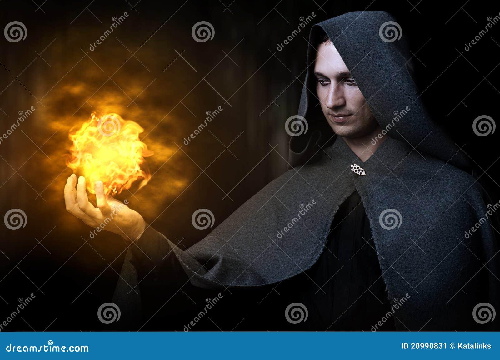 Conceito de Halloween. Feiticeiro masculino com bola de fogo