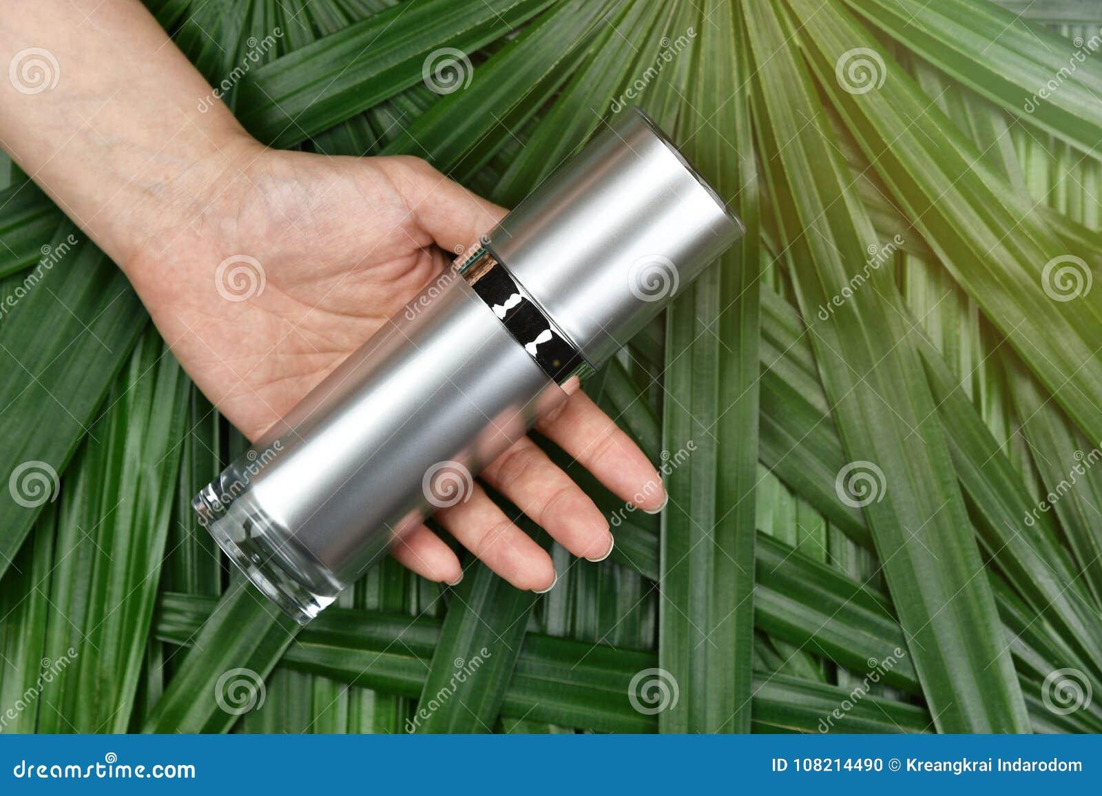 Conceito de produto natural da beleza do skincare, recipientes cosméticos da garrafa à disposição no fundo erval verde das folhas
