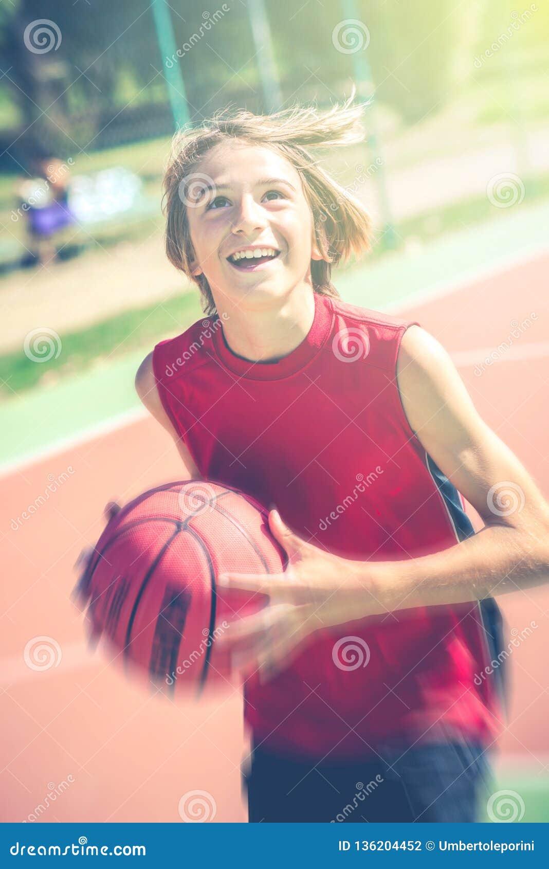 Conceito desportivo saudável exterior do estilo de vida dos adolescentes do basquetebol feliz do jogo do adolescente na mola ou n