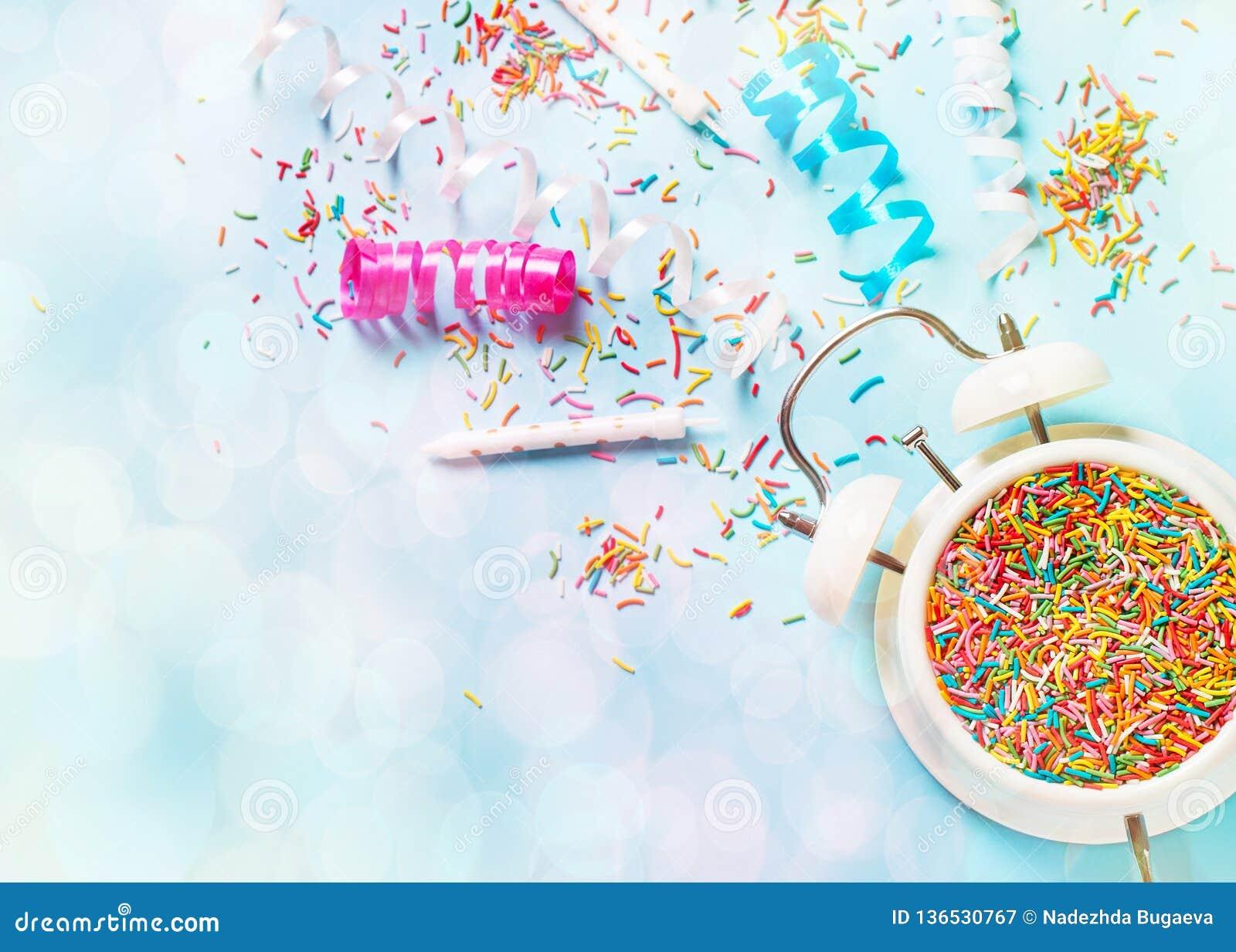 Conceito do aniversário e do tempo do partido no bakground pastel azul com alarme