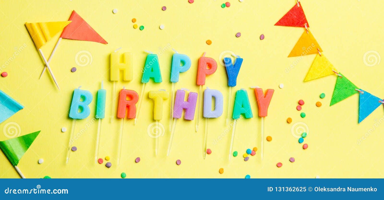 Conceito do aniversário - velas com letras 'feliz aniversario 'e confetes